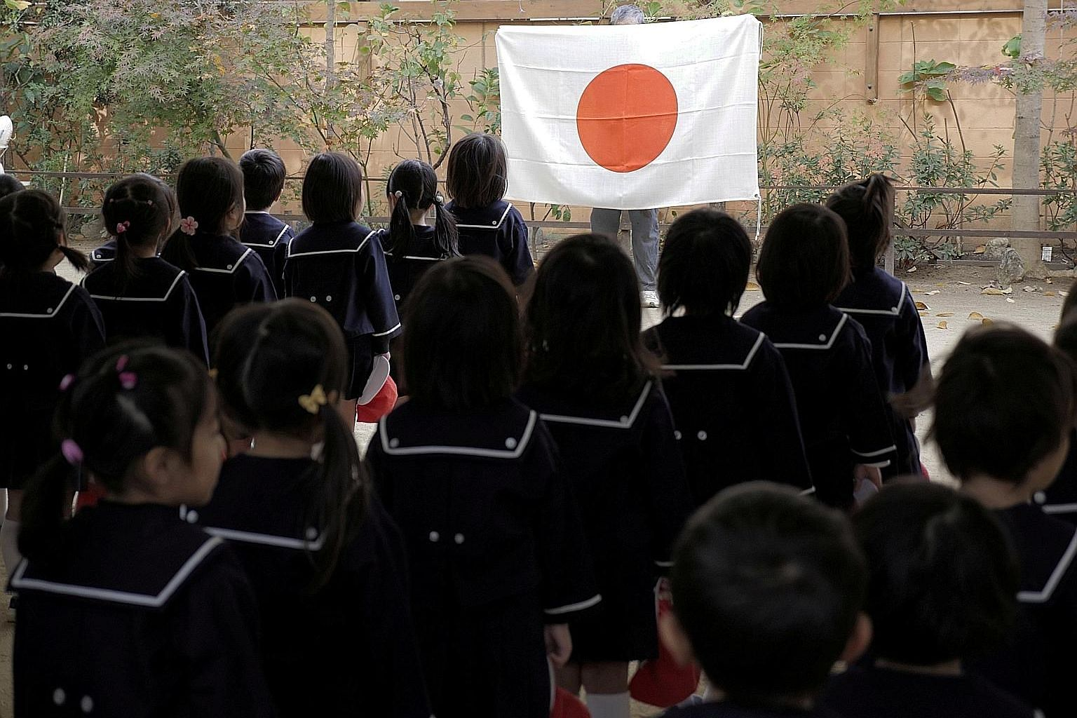 Pupils before the Japanese flag during assembly at the Tsukamoto Kindergarten in Osaka.