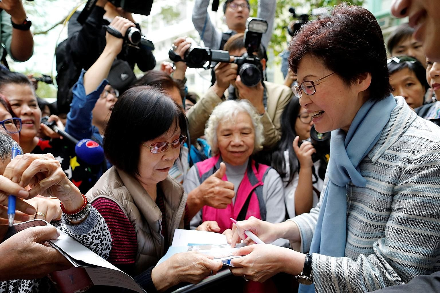 "Chief executive candidate Lam signing autographs for her fans on Thursday. The former chief secretary wrote that Hong Kongers should ""come together again for the city we love"" in an advertisement in the Post yesterday. Chief executive candidate Tsang"