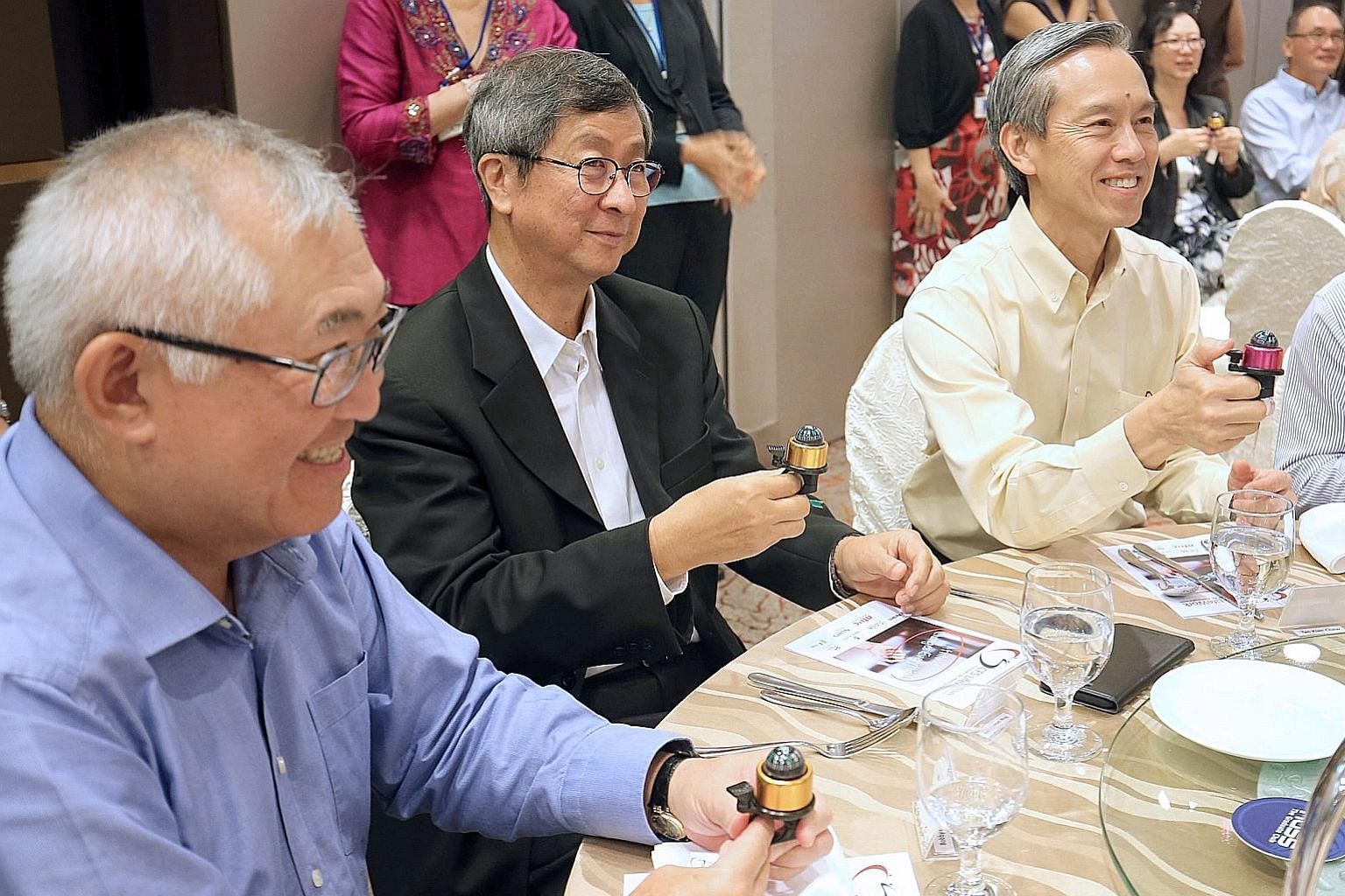 Former labour chief Lim Boon Heng (centre), with FairPrice chairman Bobby Chin (far left) and Centre For Seniors chairman Tan Kian Chew, ringing a compass bell yesterday to launch a training programme by the Centre For Seniors.