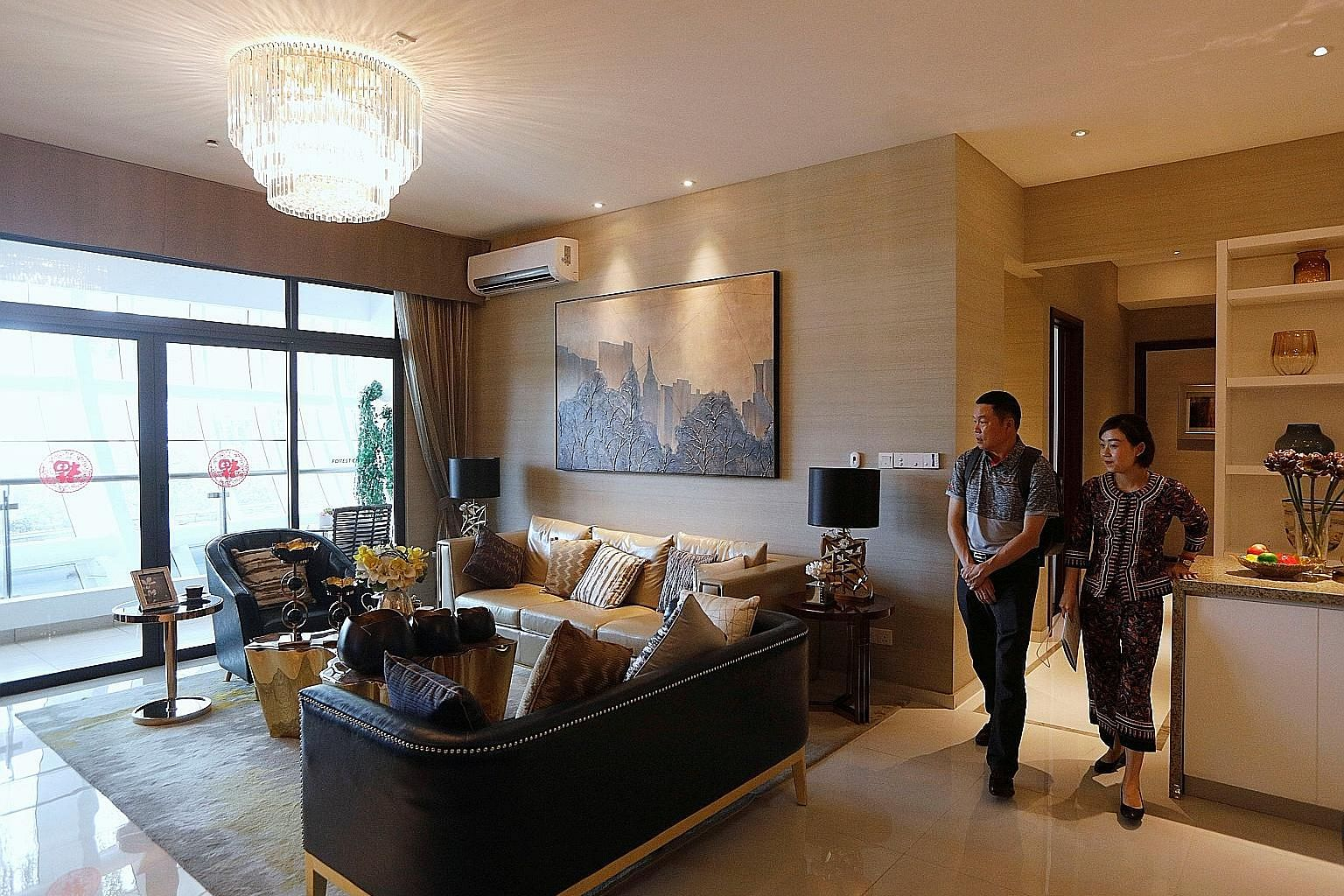 A sales agent taking a prospective buyer on a tour of a show flat at Country Garden's Forest City in Johor Baru. Hundreds of Chinese investors have bought units in the residential project, and they are affected by China's new limits on the ways they