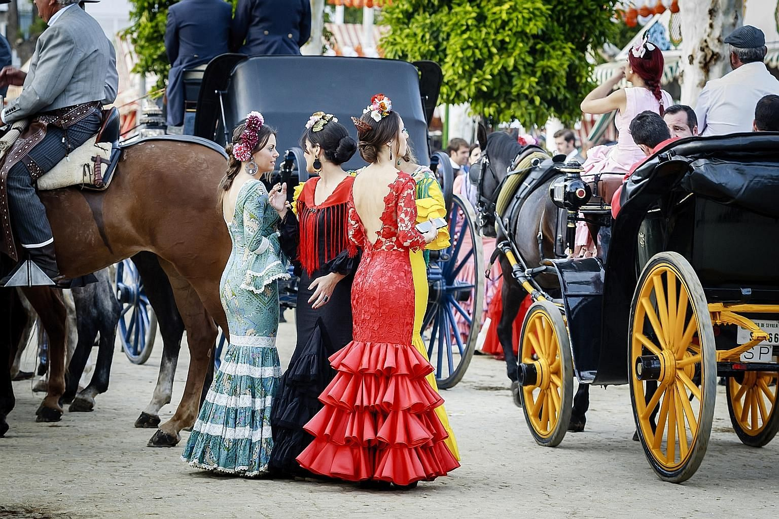 Top: Women in traditional flamenco dress at the Feria de Abril, or April Fair, in Seville, Spain. Above: Bask in Native American music and culture at the New Orleans Jazz & Heritage Festival.