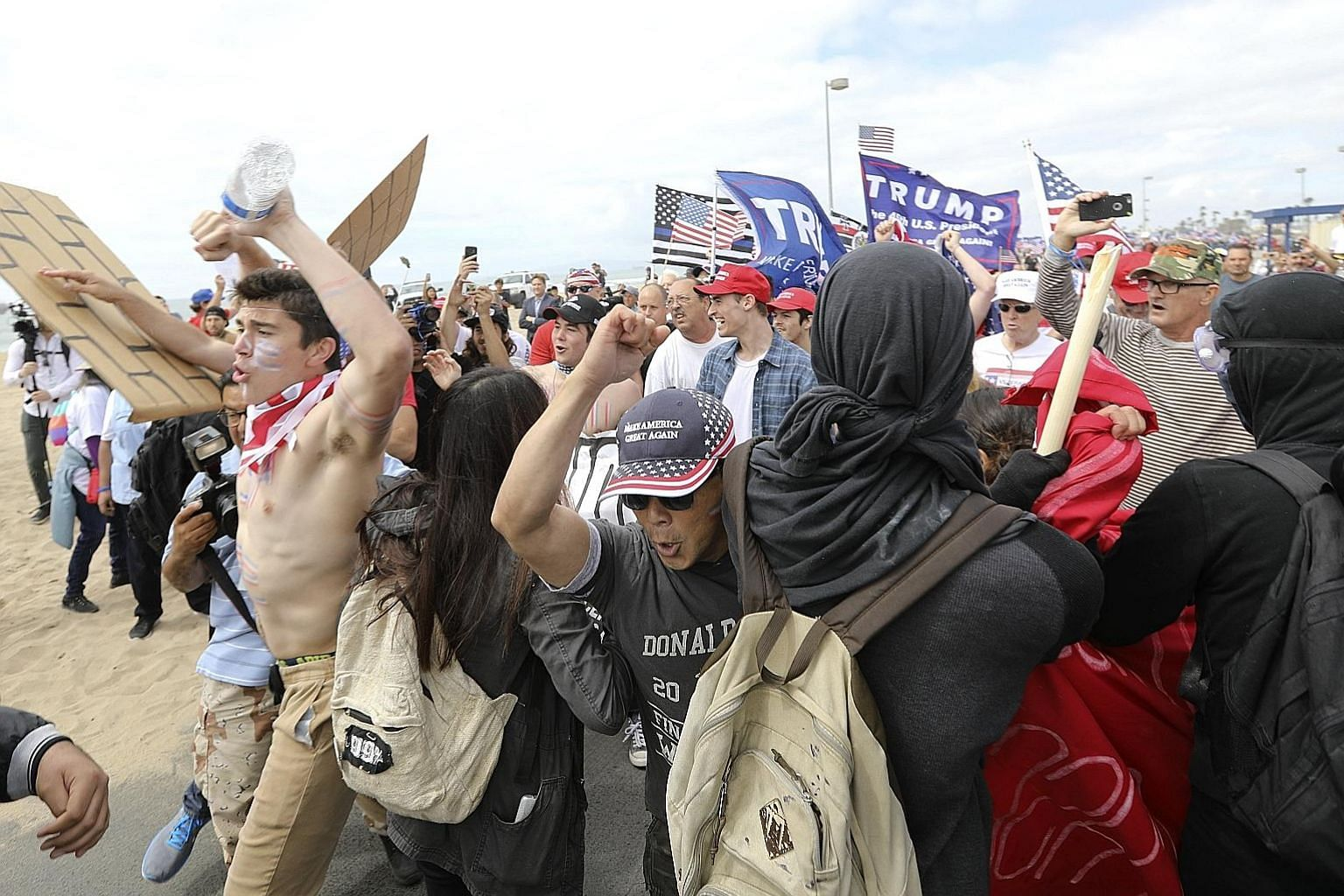 Trump supporters breaking through a human wall of anti-Trump protesters during a rally in Huntington Beach, California, last Saturday. Support for Mr Trump appeared unflagging despite the collapse of his campaign promise to overhaul the healthcare sy