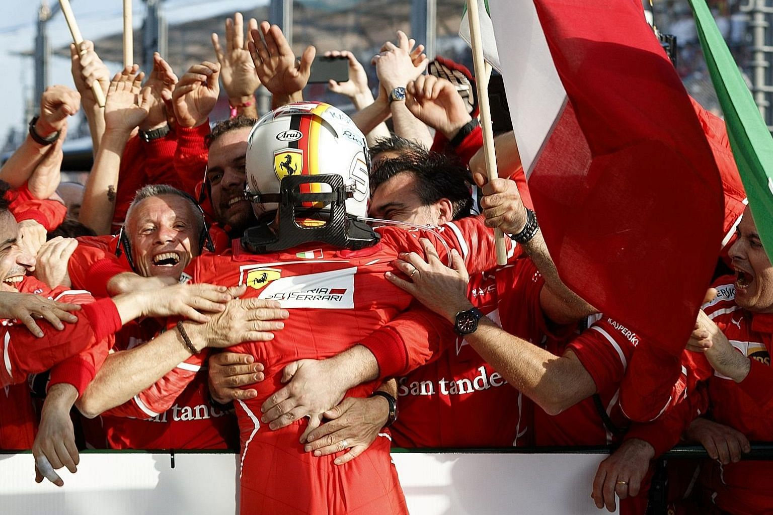 Ferrari driver Sebastian Vettel being mobbed by his team members after winning the Formula One season-opening Australian Grand Prix in Melbourne yesterday. The German beat Mercedes rival Lewis Hamilton by almost 10 seconds for his first race win sinc