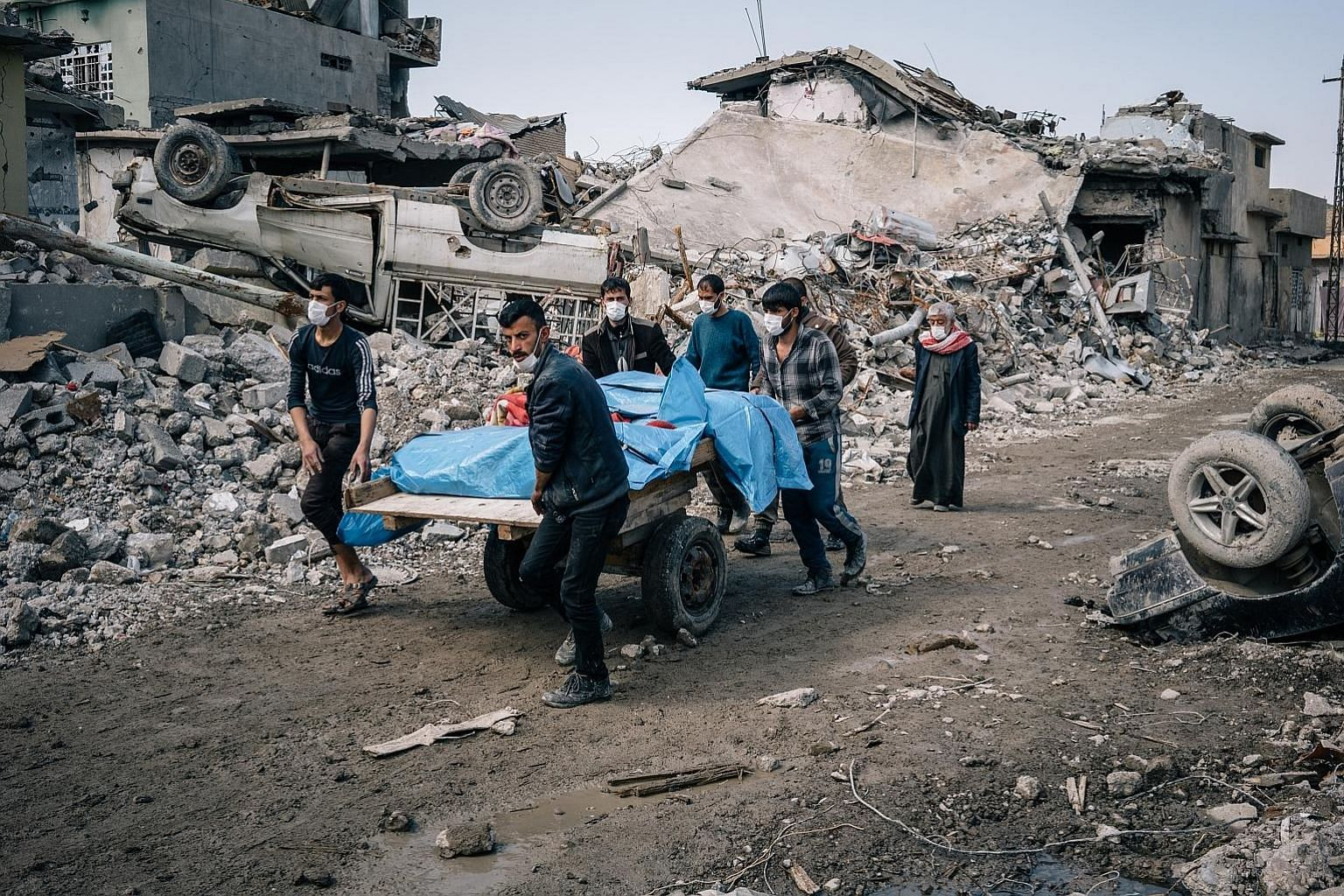 Volunteers carting away the bodies of civilians found among the rubble of a collapsed building in Mosul's al Jadida district.