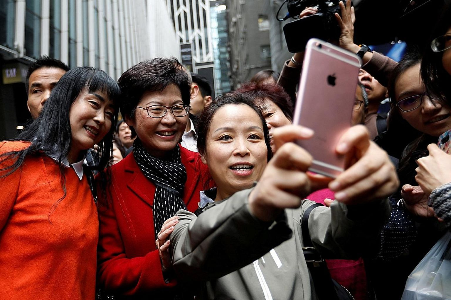 Supporters clamouring for souvenir shots with Mrs Carrie Lam, a day after she was elected as the new Chief Executive in Hong Kong on Sunday. Mrs Lam has vowed to heal political divisions but the decision to prosecute nine pro-democracy activists has