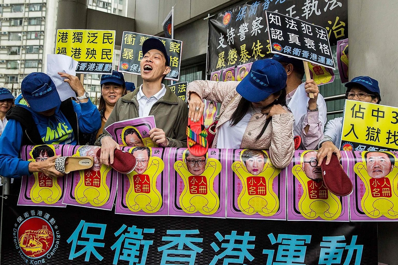 Pro-government protesters using slippers to beat pictures of the leaders of the Occupy Central movement outside the Eastern District Court yesterday. Nine activists involved in the 2014 protests were charged yesterday.