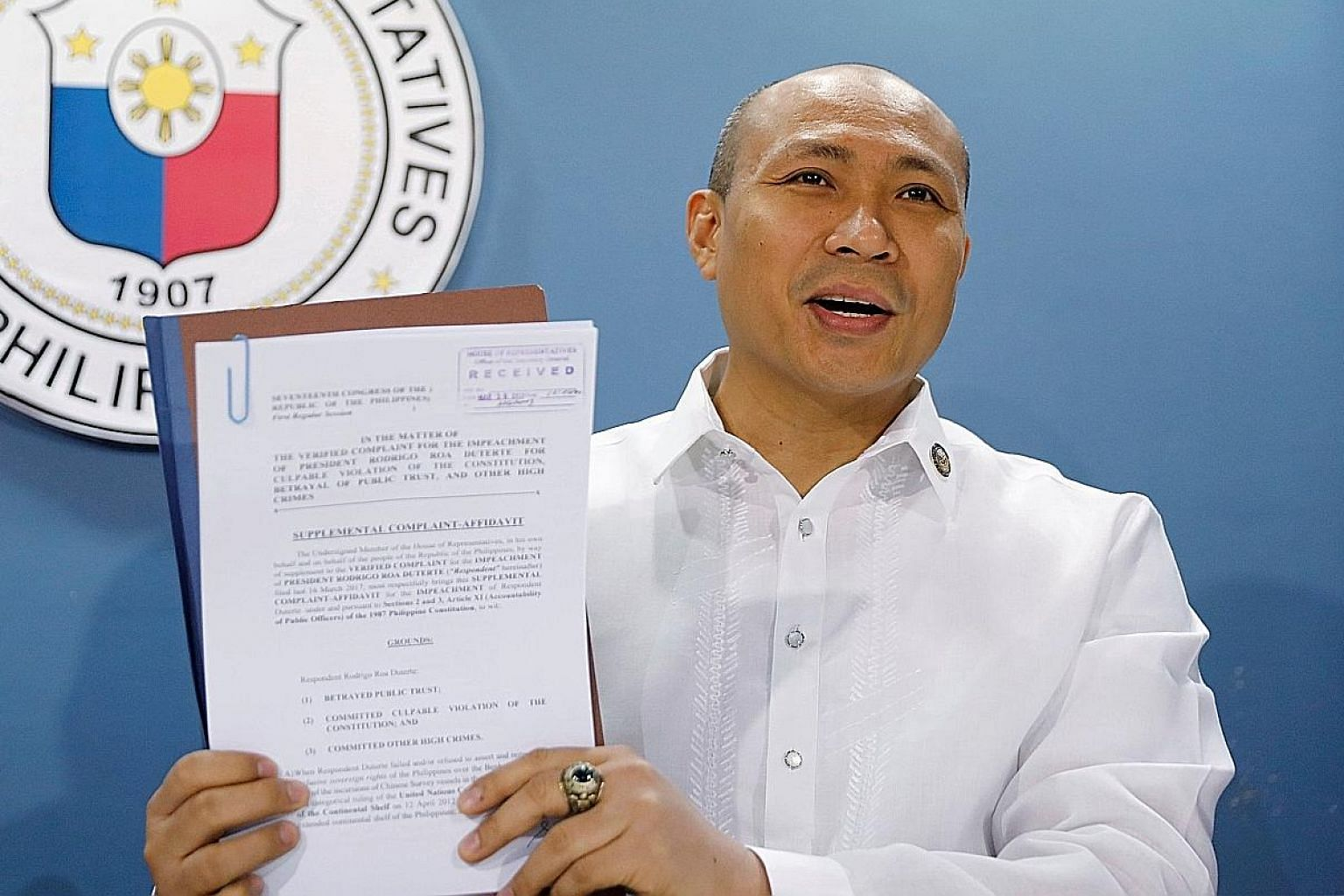 "Representative Gary Alejano showing the media a copy of a supplemental impeachment complaint against President Rodrigo Duterte yesterday, over the latter's ""defeatist stance"" in the territorial dispute with China."