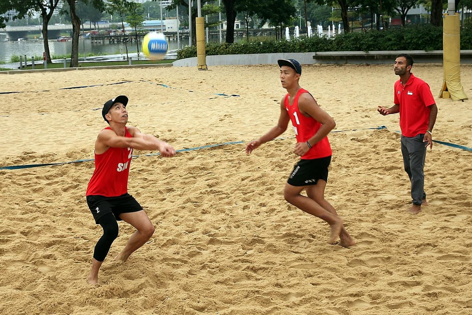 Gilbert Tan setting the ball for Zhuo Hong Chuan in training, as national beach volleyball coach Dean Martin instructs them. The Canadian has targeted a top-six placing in Asia for Singapore to stand a chance of competing in both the Asian and Common