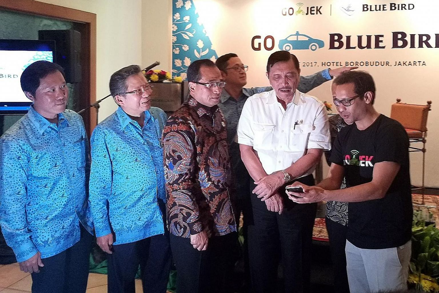 Coordinating Maritime Affairs Minister Luhut Pandjaitan (in white) at the launch of a collaboration between Go-Jek and Blue Bird yesterday. He is flanked by Go-Jek chief executive Nadiem Makarim (in black T-shirt) and Transport Minister Budi Karya. A