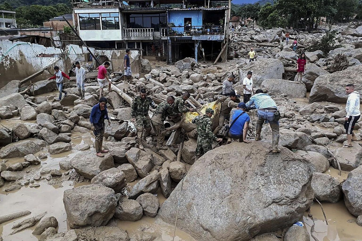 Cars and houses were damaged after a landslide in Colombia's south-western province of Putumayo. Rescue efforts in Mocoa are still ongoing (right) with an unknown number of people missing after heavy rain overnight caused several rivers to overflow.