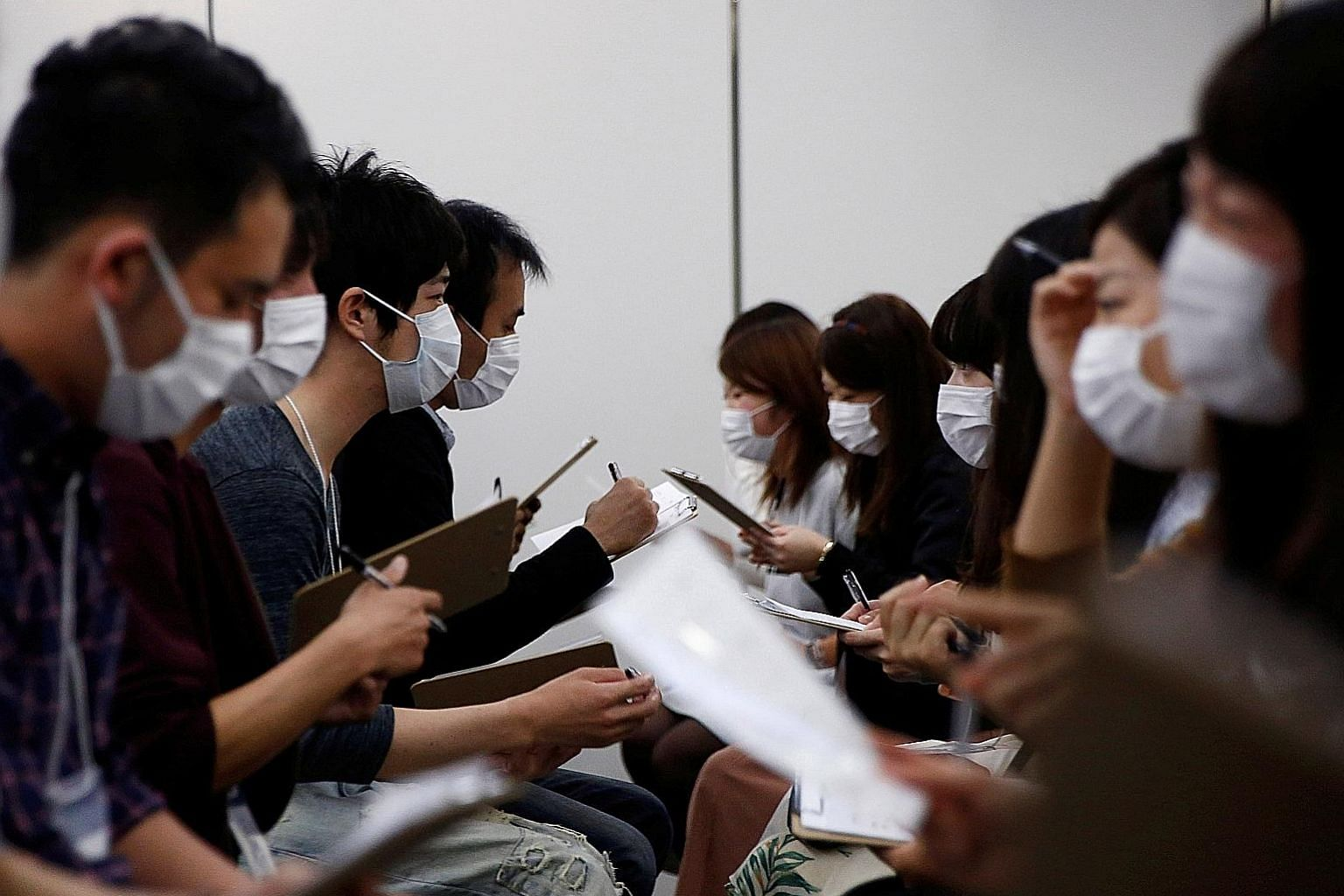 Masked matchmaking events - like this one (far left) in Tokyo last October - aim to encourage participants to get to know each other without being judged on looks. (Left) Spring in Tokyo comes with blooming cherry blossoms and hay fever, which affect