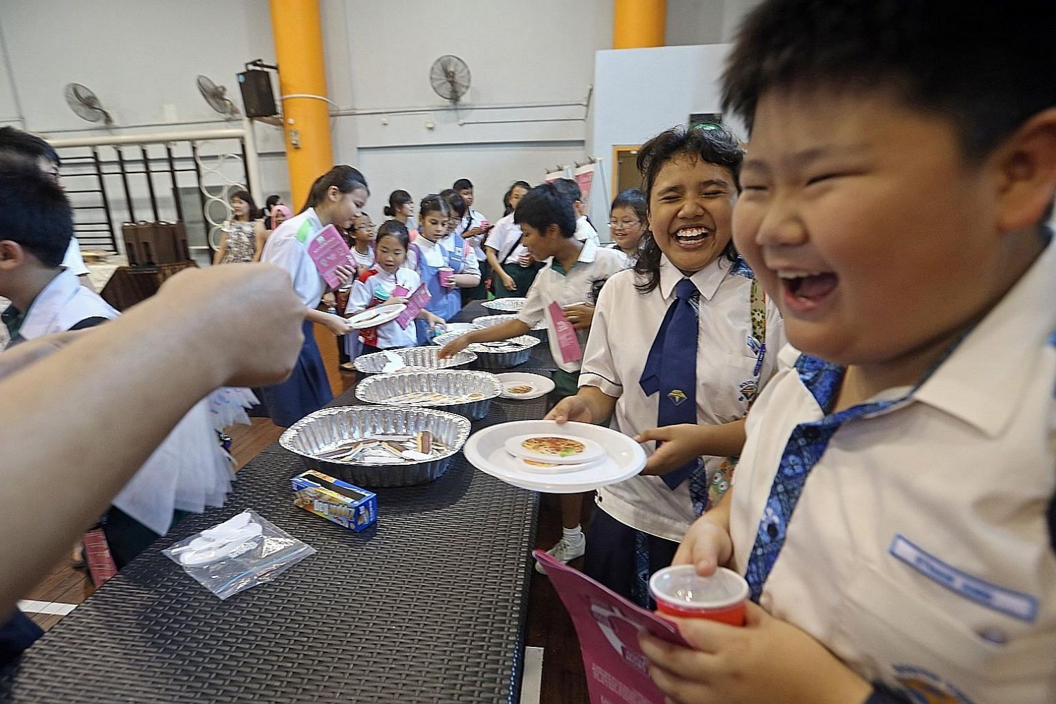 Ethan Ang and Siti Syazwana of South View Primary School, both 11, participating in a game at a station on the educational trail yesterday. The simulated buffet highlights the importance of not wasting food.