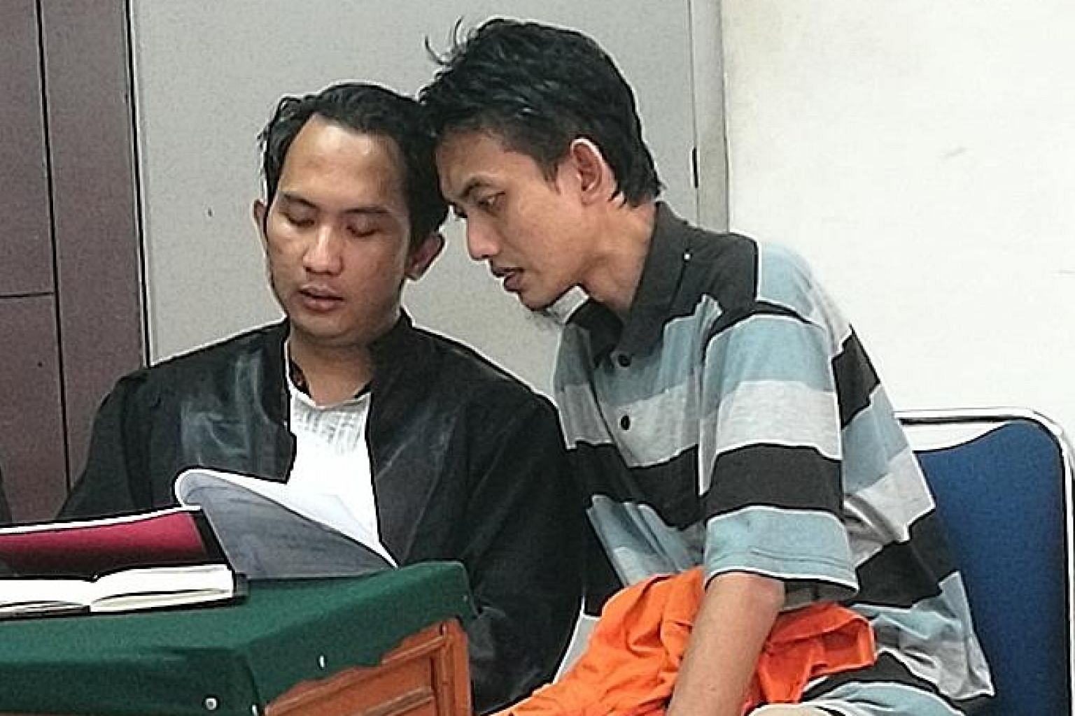 Alleged terrorist cell leader Gigih Rahmat Dewa (in striped shirt) with his lawyer during his trial in a Jakarta courtroom on Saturday.