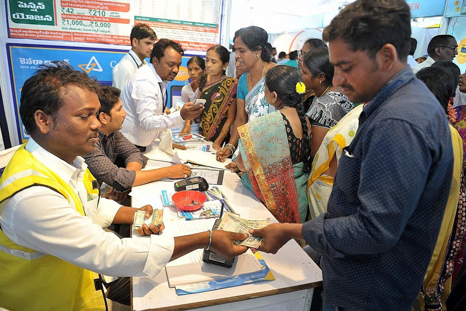 At an event to promote digital transactions, a visitor who had used Aadhaar to withdraw money from his bank account receives the cash from a bank employee. Held in January, it was part of the Digi Dhan Mela initiative to create a digital economy.