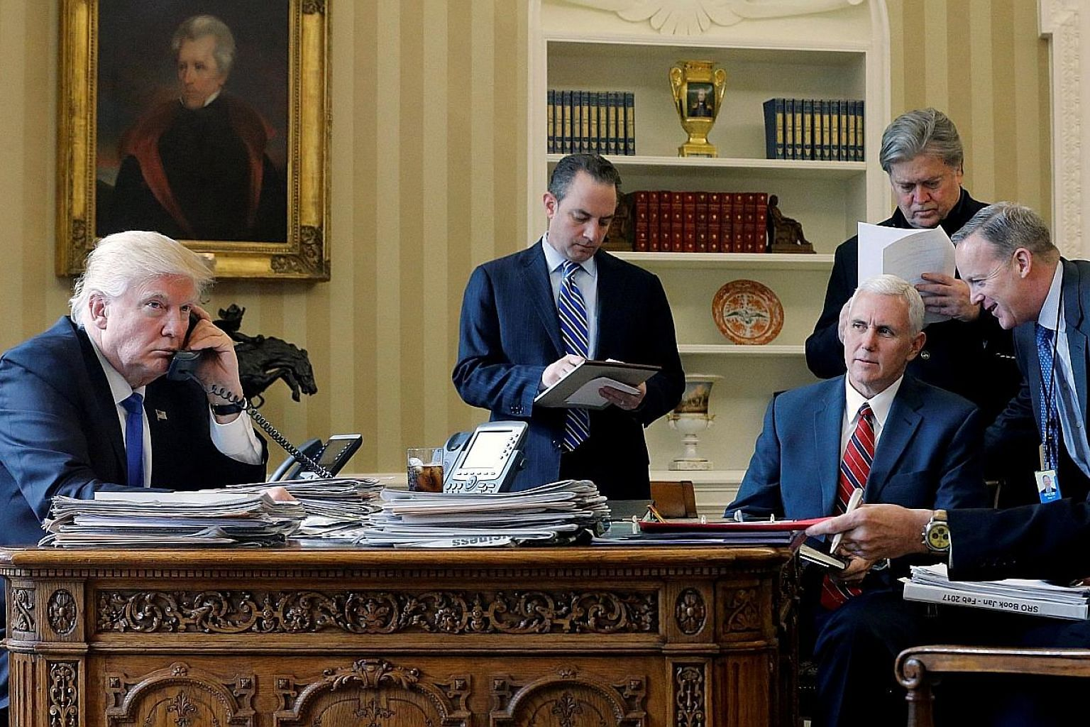 Mr Donald Trump on the phone with Mr Vladimir Putin (below) in January, in the presence of (from left) White House Chief of Staff Reince Priebus, Vice-President Mike Pence, chief strategist Steve Bannon and press secretary Sean Spicer.