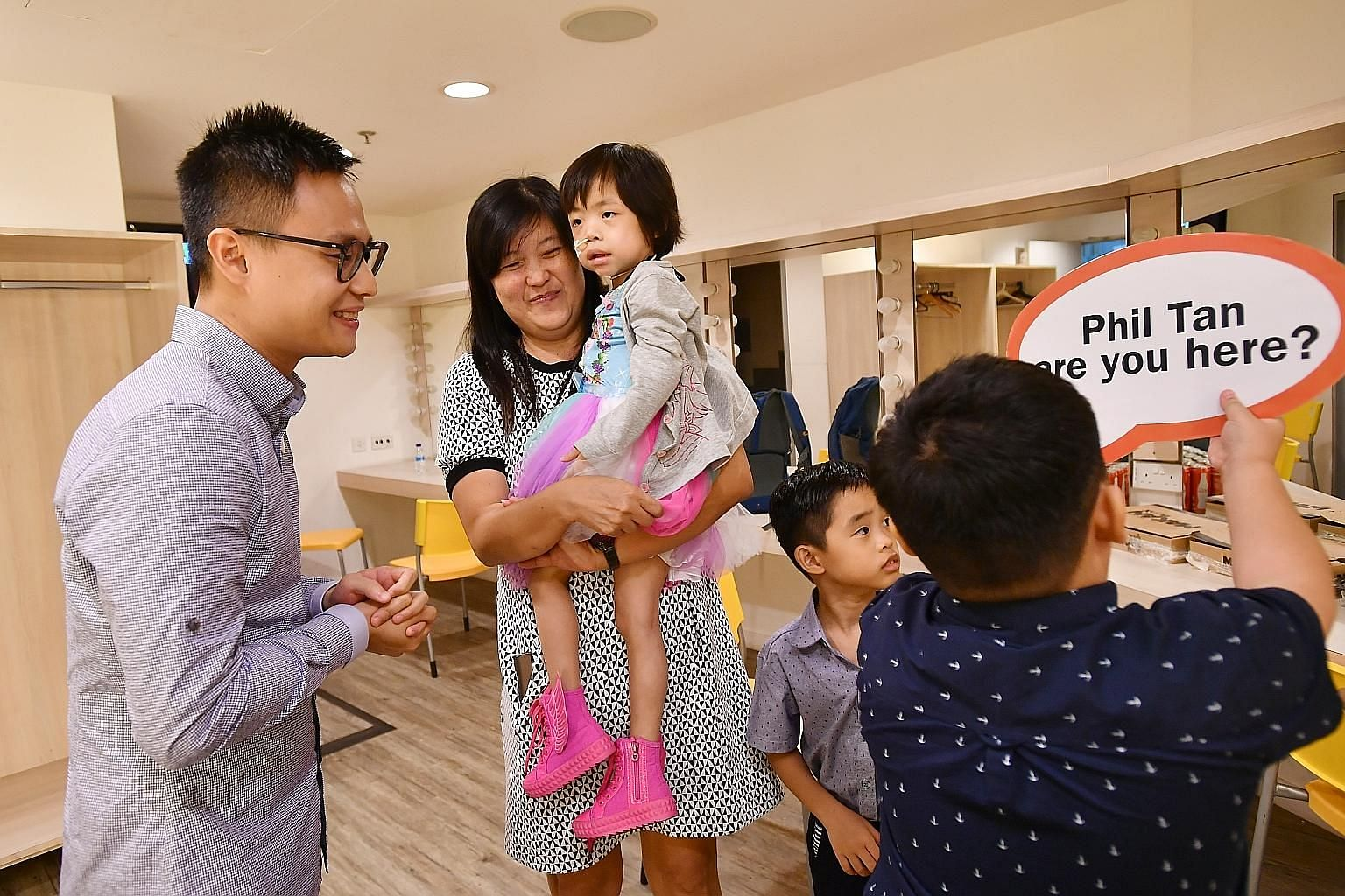 Mr Phil Tan met Ryssa and her family - mother Doris Tia, 42, and brothers Kieran (back to camera) and Kaiser - yesterday. The children are eight-year-old triplets, and Mr Tan's bone marrow saved Ryssa's life.