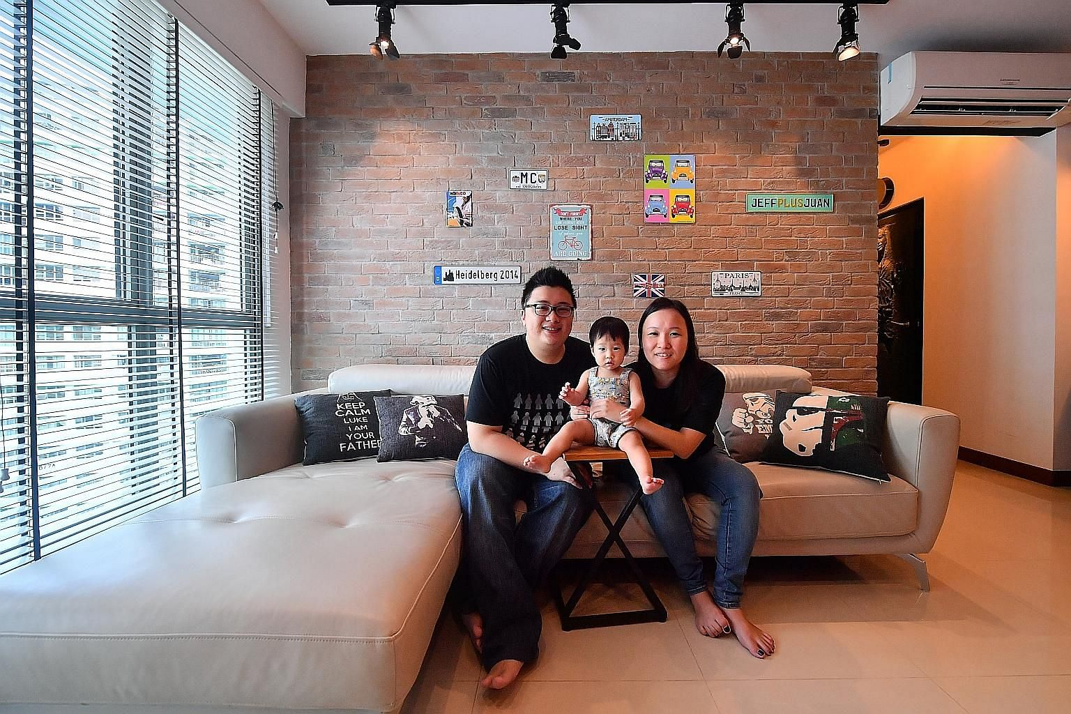 The living room of Mr Jefferson Lee and Ms Sheryl Tian (far left, with their daughter Aletheia) has red shipping container-inspired storage which displays their knick-knacks and toys.