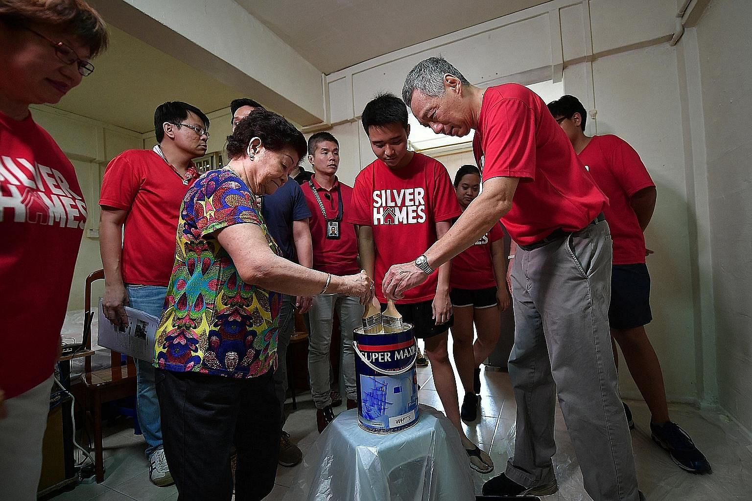Prime Minister Lee Hsien Loong helping Madam Chen Yueh Lun paint her one-room rental flat together with student volunteers. With them is Central Singapore District Mayor Denise Phua (far left).