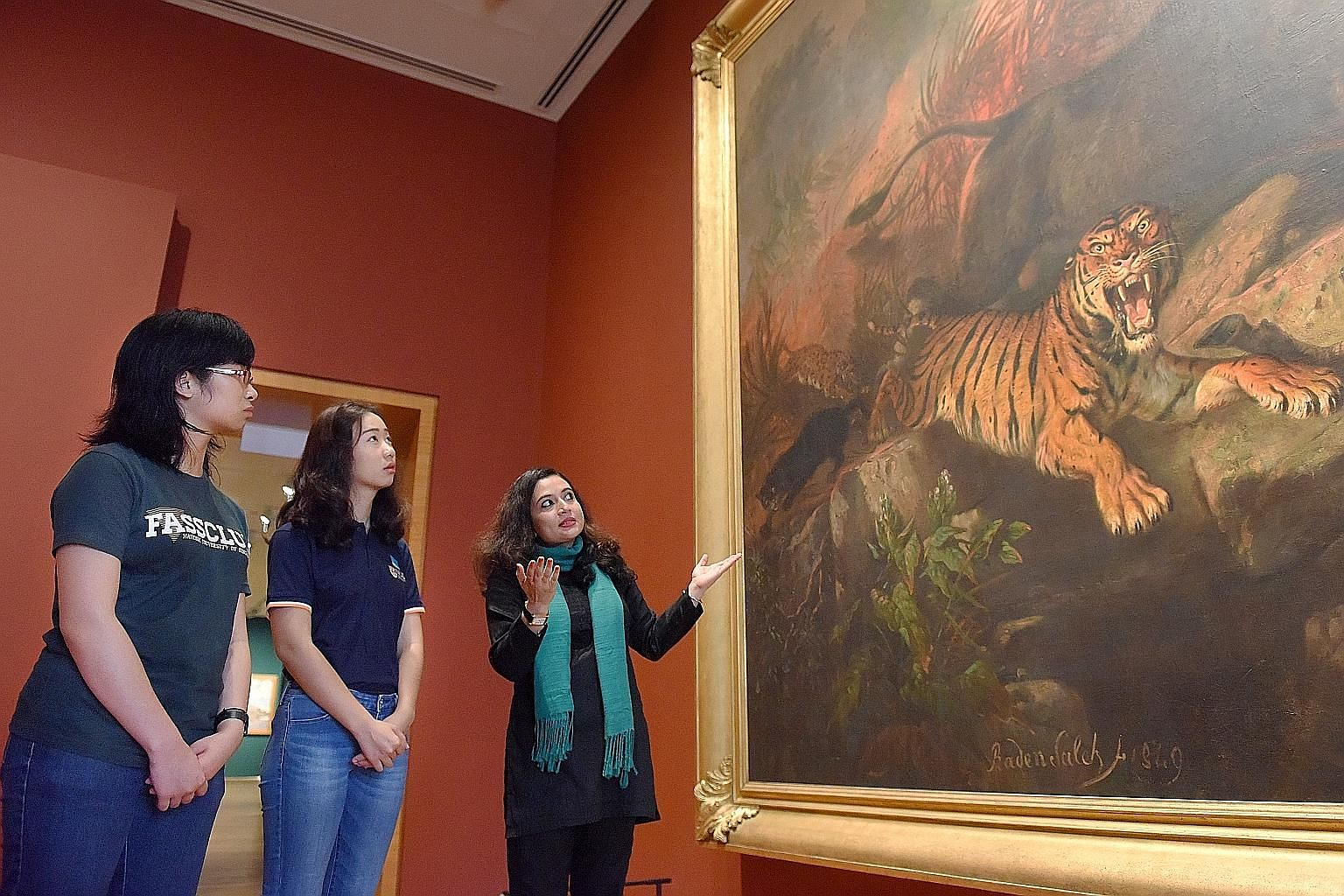 Dr Priya Maholay-Jaradi analysing Indonesian artist Raden Saleh's painting Forest Fire with two of her students, Ms Hor Jen Yee (left) and Ms Chen Wenting, who had taken an introductory module on art history.