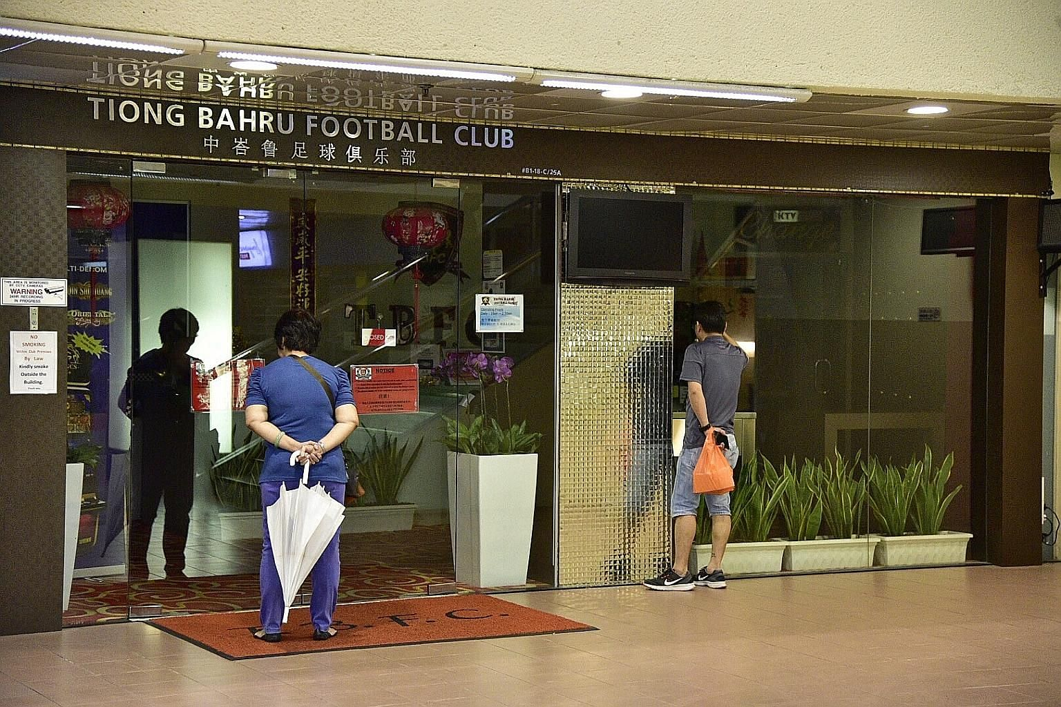 A man and a woman looking in on the Tiong Bahru FC clubhouse at People's Park Centre yesterday. It has been closed since Thursday's CAD raid.