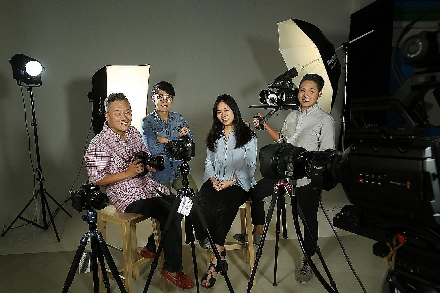 "Alan Photo founder Alan Tan with his nephew, Bin Ming (with glasses); daughter, Audrey; and son, Alvan. They are in the studio section of their new ""experience store"" dubbed REC by Alan Photo in CT Hub 2 in Lavender Street. The 3,000 sq ft store come"