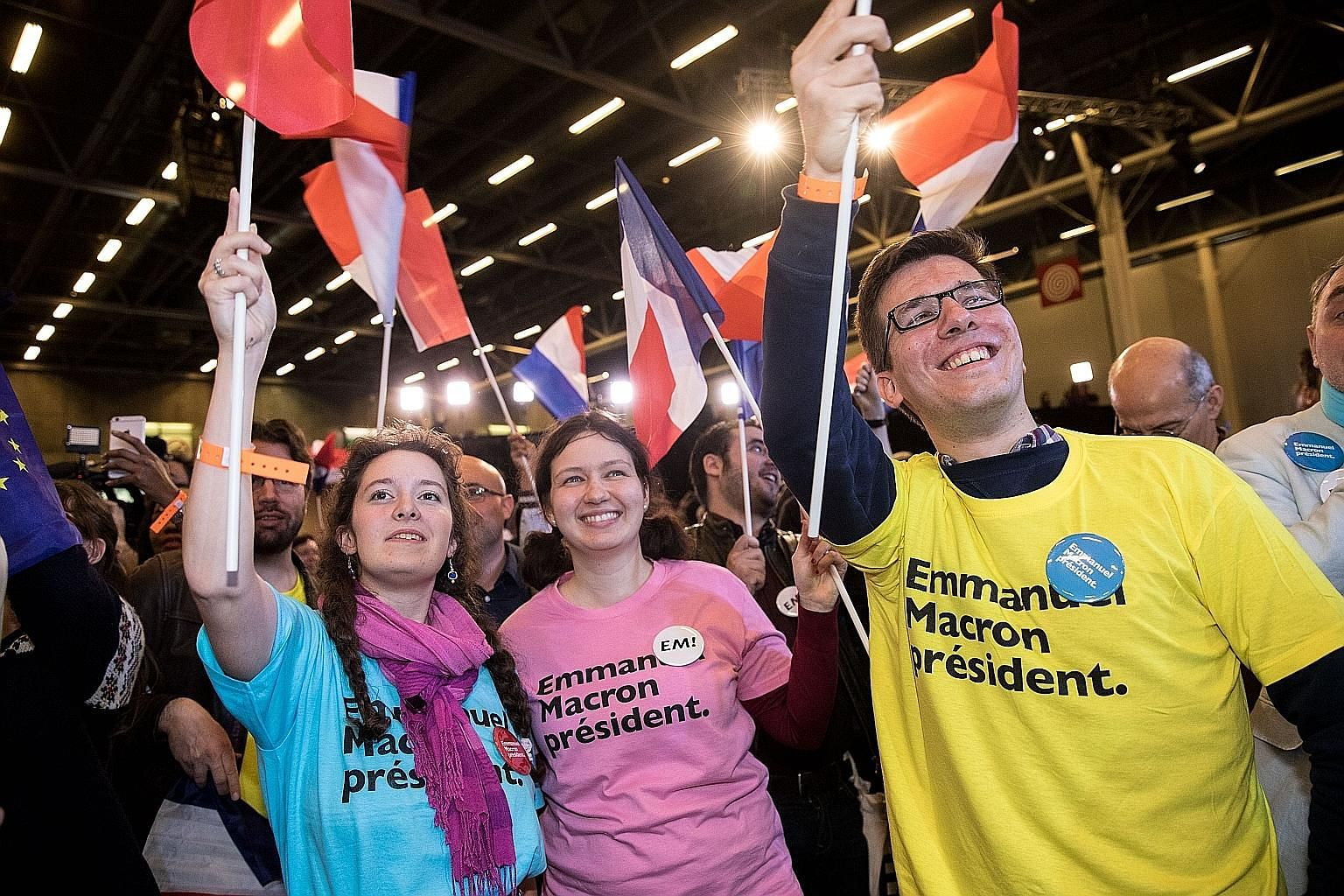 Supporters of Mr Emmanuel Macron and Ms Marine Le Pen at the En Marche! HQ (top right) and at a National Front party celebrating Sunday's results.