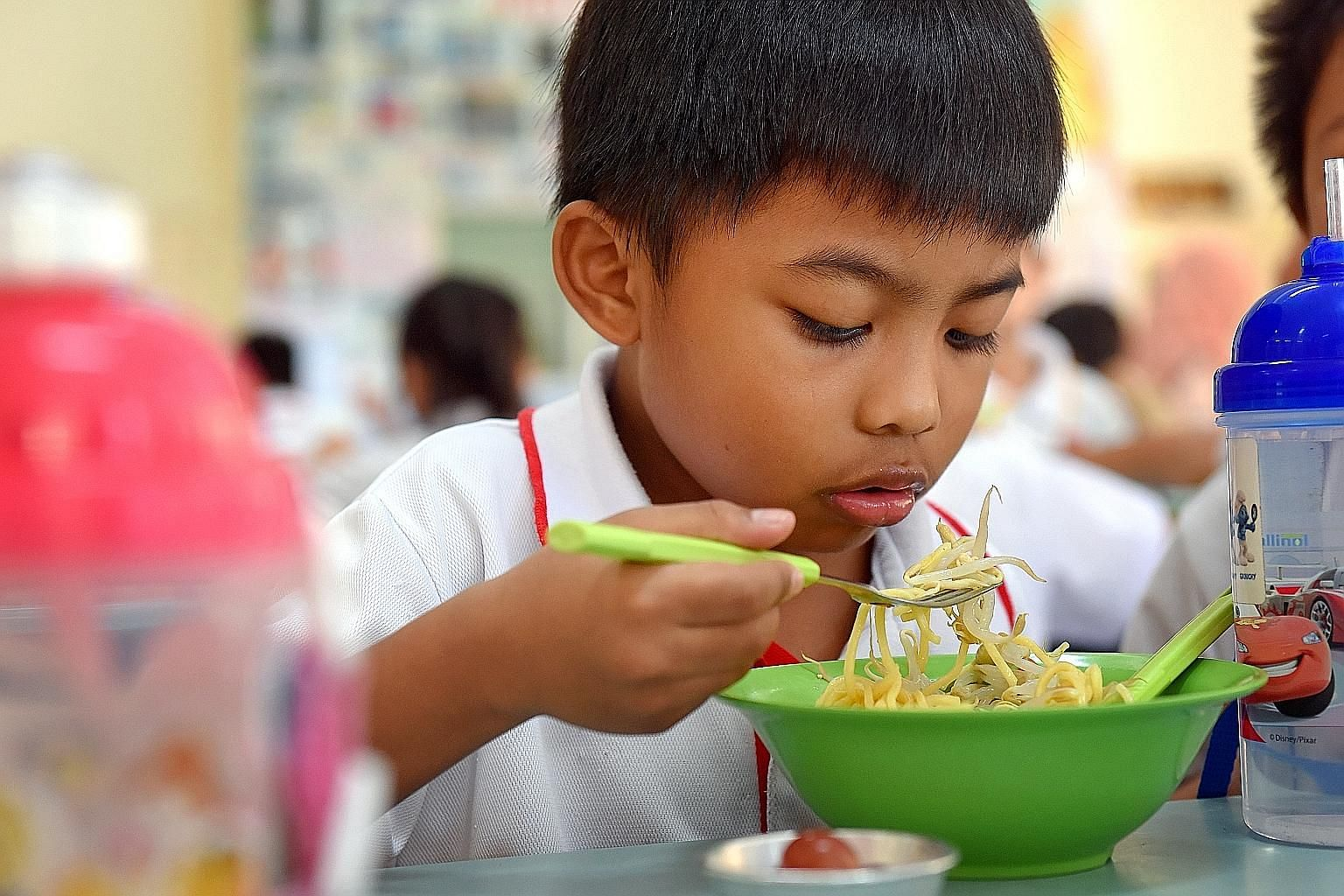 Bedok Green Primary 1 pupil Ziekriy Hannan Khairul Amin eating a bowl of noodles with bean sprouts. The school makes sure that healthy dishes look similar to the original versions, and limits the sale of snacks.