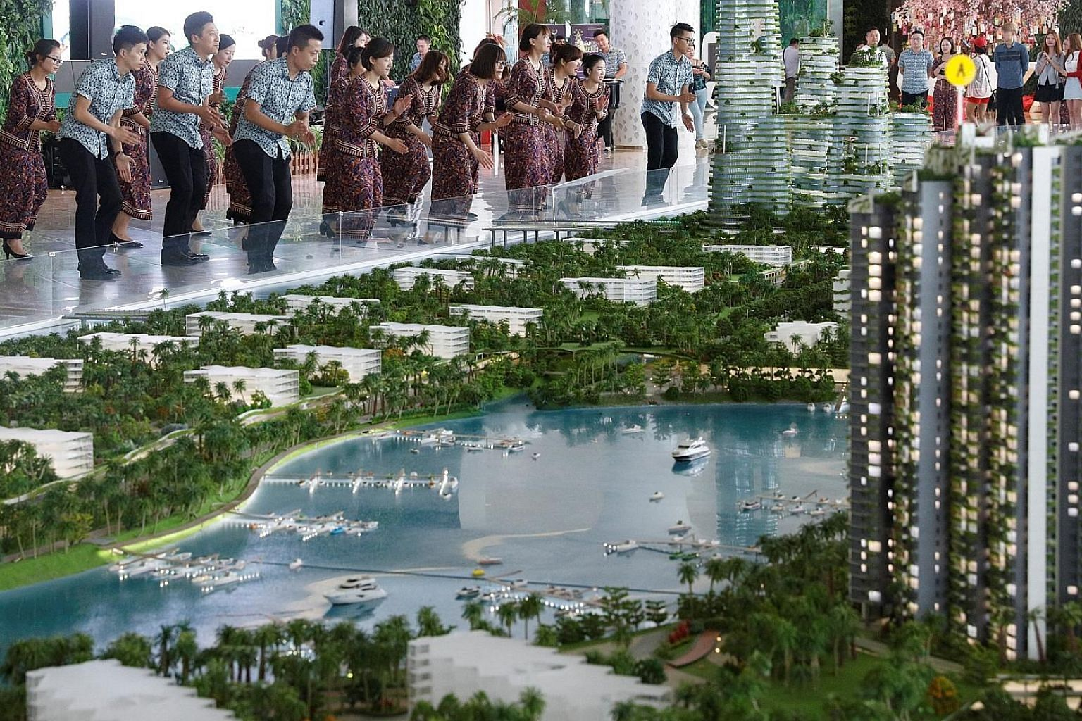 Sales agents, mostly from China, dressed in traditional Malaysian batik and entertaining visitors at Chinese property developer Country Garden's Forest City showroom in Johor Baru in February this year. China is now the largest investor in Malaysia,