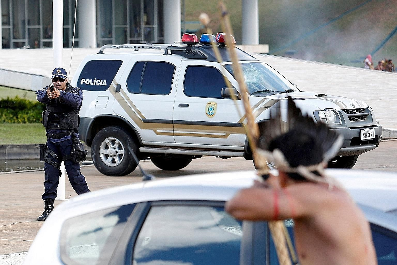 A policeman facing off against a member of an indigenous tribe in Brazil during a protest over land rights on Tuesday.