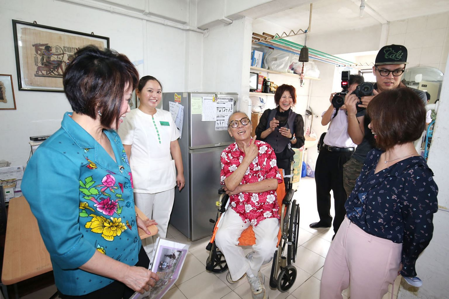 Mr Wong Ah Ann, 68, a beneficiary of a newly launched community care programme, sharing his experience with Dr Lily Neo (in light blue), an MP for Jalan Besar GRC, and Senior Minister of State for Health Amy Khor (far right). Yesterday, SingHealth Regiona