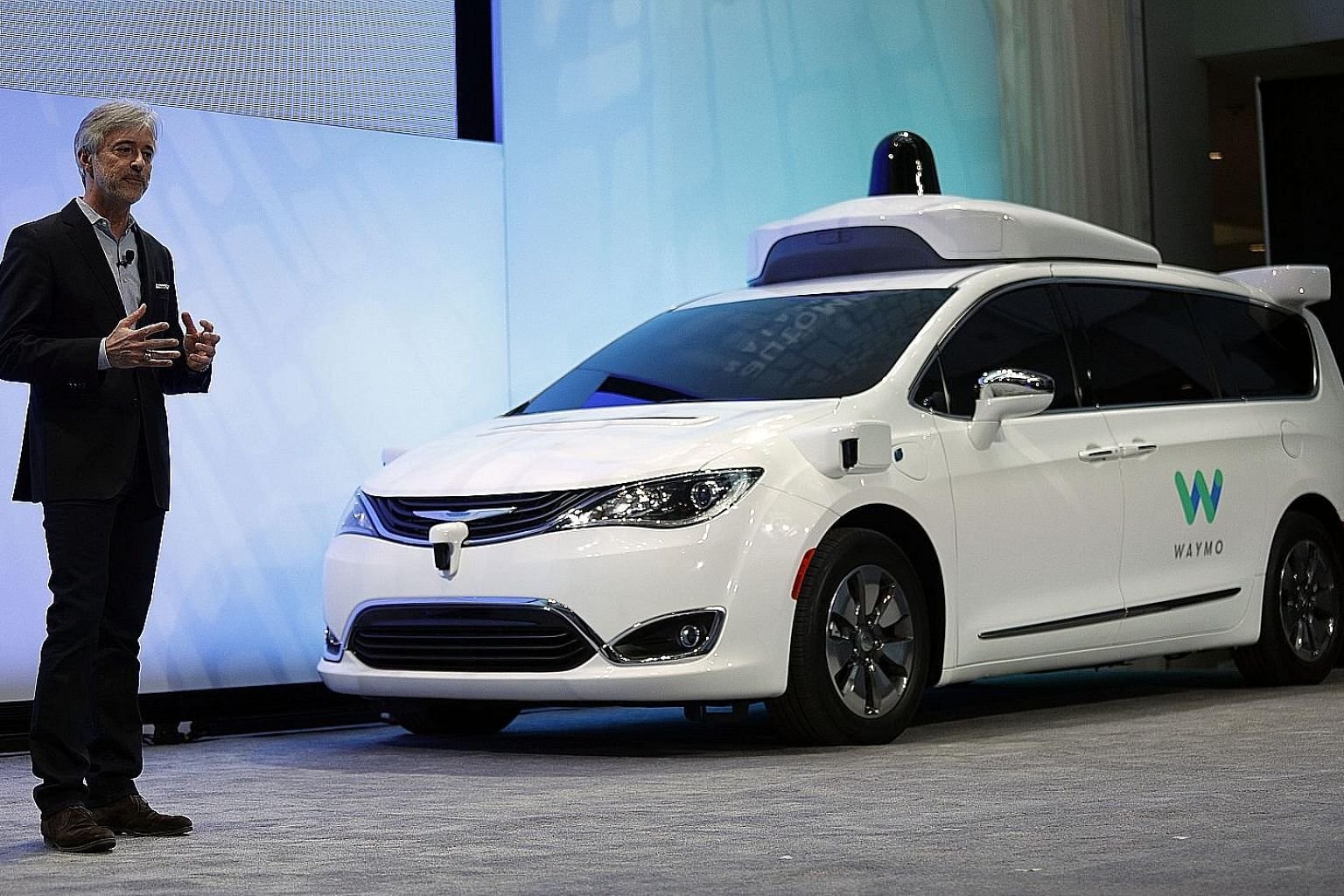 Alphabet Inc's self-driving car unit Waymo's chief executive officer John Krafcik with a customised Chrysler Pacifica Hybrid. Initial users will be able to book the minivans with an app for free.