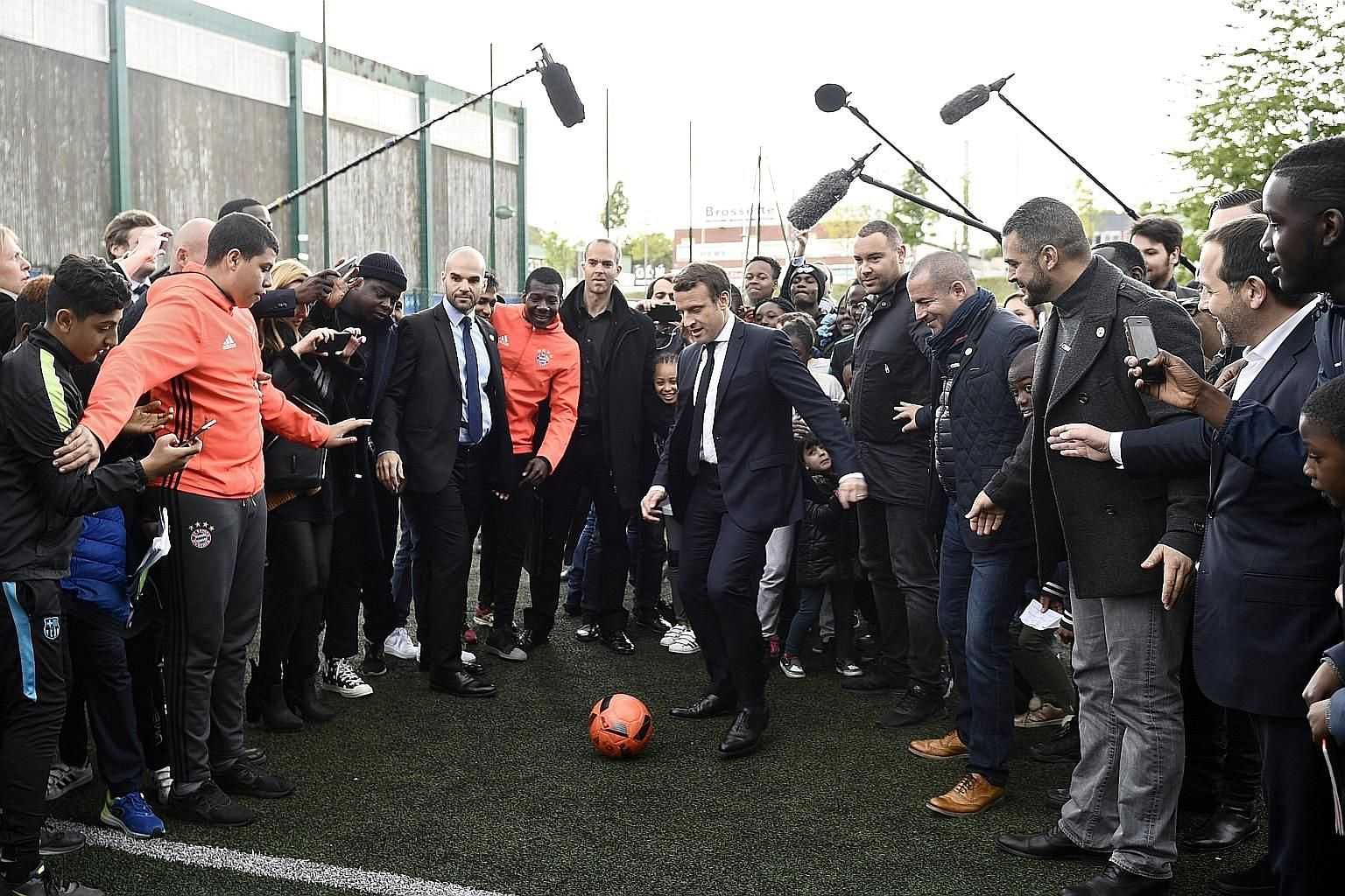 French presidential candidate Emmanuel Macron kicking a football during a campaign visit to Sarcelles, north Paris, on Thursday. The camp has accused Russia of attacking its databases, fuelling suspicions that the Kremlin is trying to undermine the c