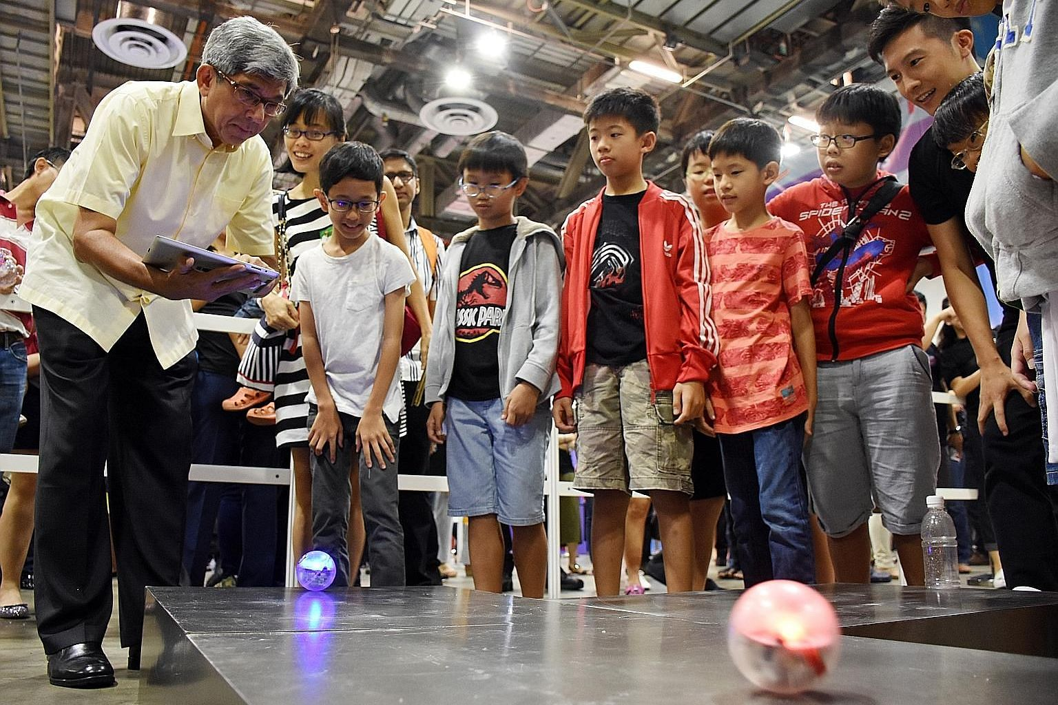 Dr Yaacob Ibrahim taking part in a game that involves navigating electronic balls with a tablet at Tech Saturday (Upsized!) yesterday. The two-day carnival focuses on products and services helping Singapore's digital economy transformation.