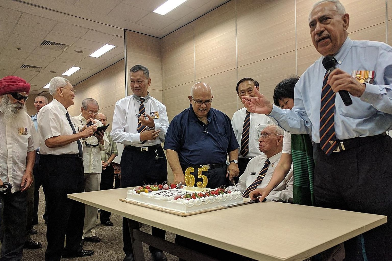 Mr Roland Simon (seated) and other veterans from the Malayan Royal Naval Volunteer Reserve's Singapore division with the anniversary cake at yesterday's lunch event.