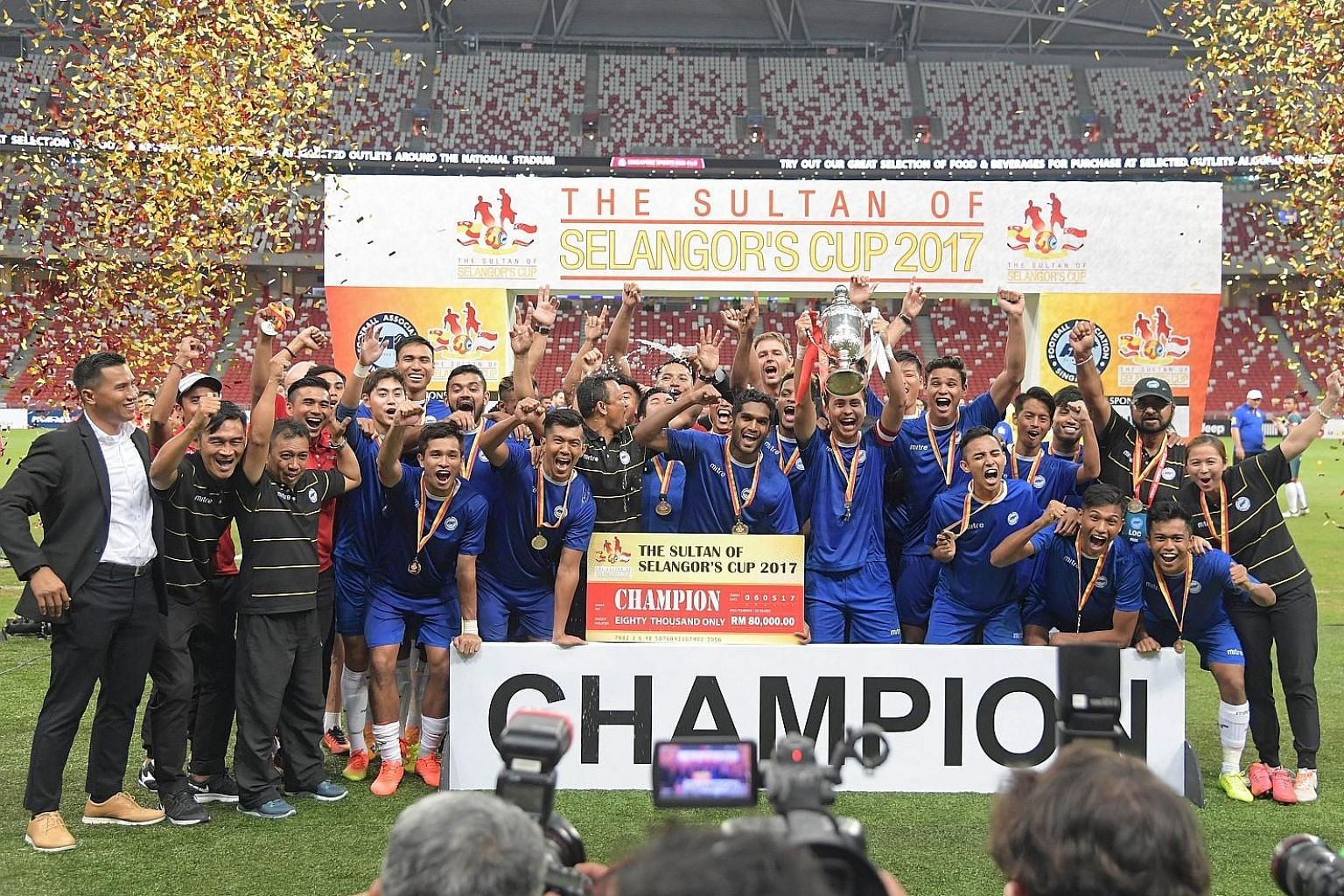 Left: The triumphant Singapore side with the Sultan of Selangor's Cup and their winners' medals after their 3-2 victory yesterday. It was Singapore's seventh win since the annual exhibition match began in 2001. Below: In the company of their player e
