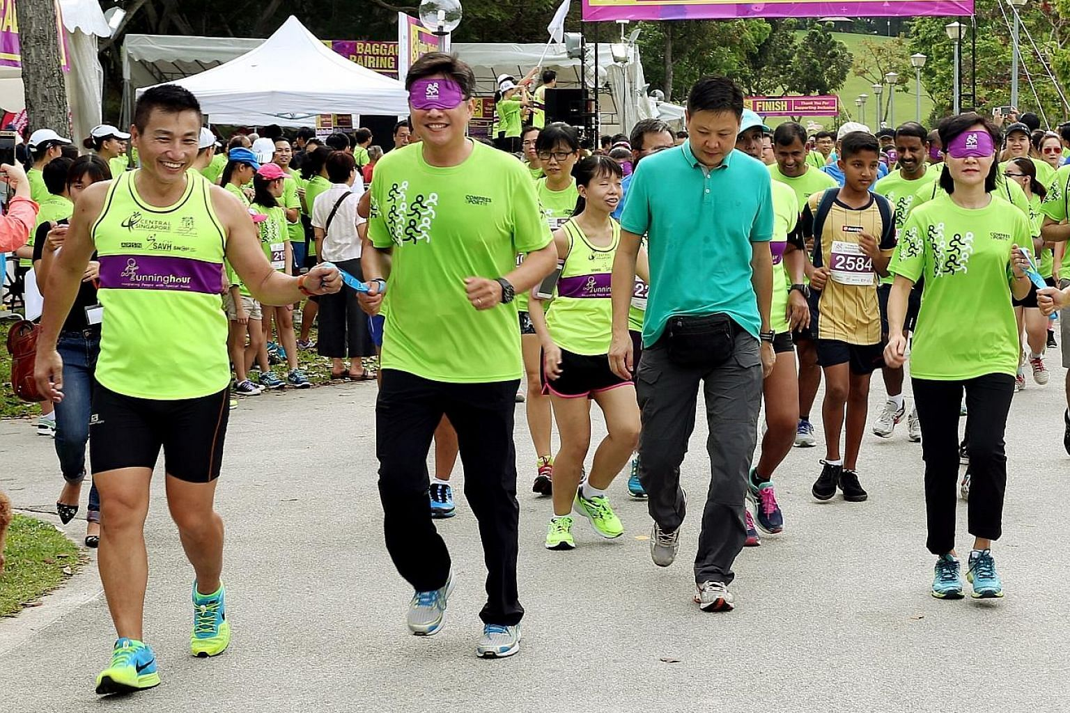 Minister for Education (Schools) Ng Chee Meng running blindfolded at yesterday's Runninghour in Bedok Reservoir, guided by group founder John See Toh. Mr Ng and his wife Michelle (right) ran for 1km.