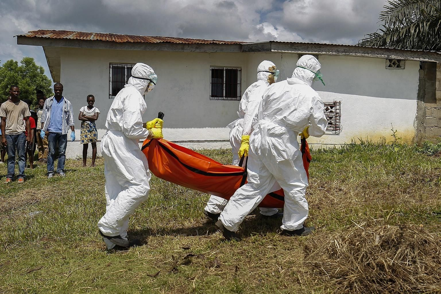 A burial team retrieving the body of a suspected Ebola victim in Banjor, on the outskirts of Monrovia, Liberia, in this October 2014 file photo. The Ebola flare-up that tore through West Africa in 2014 killed more than 11,000.