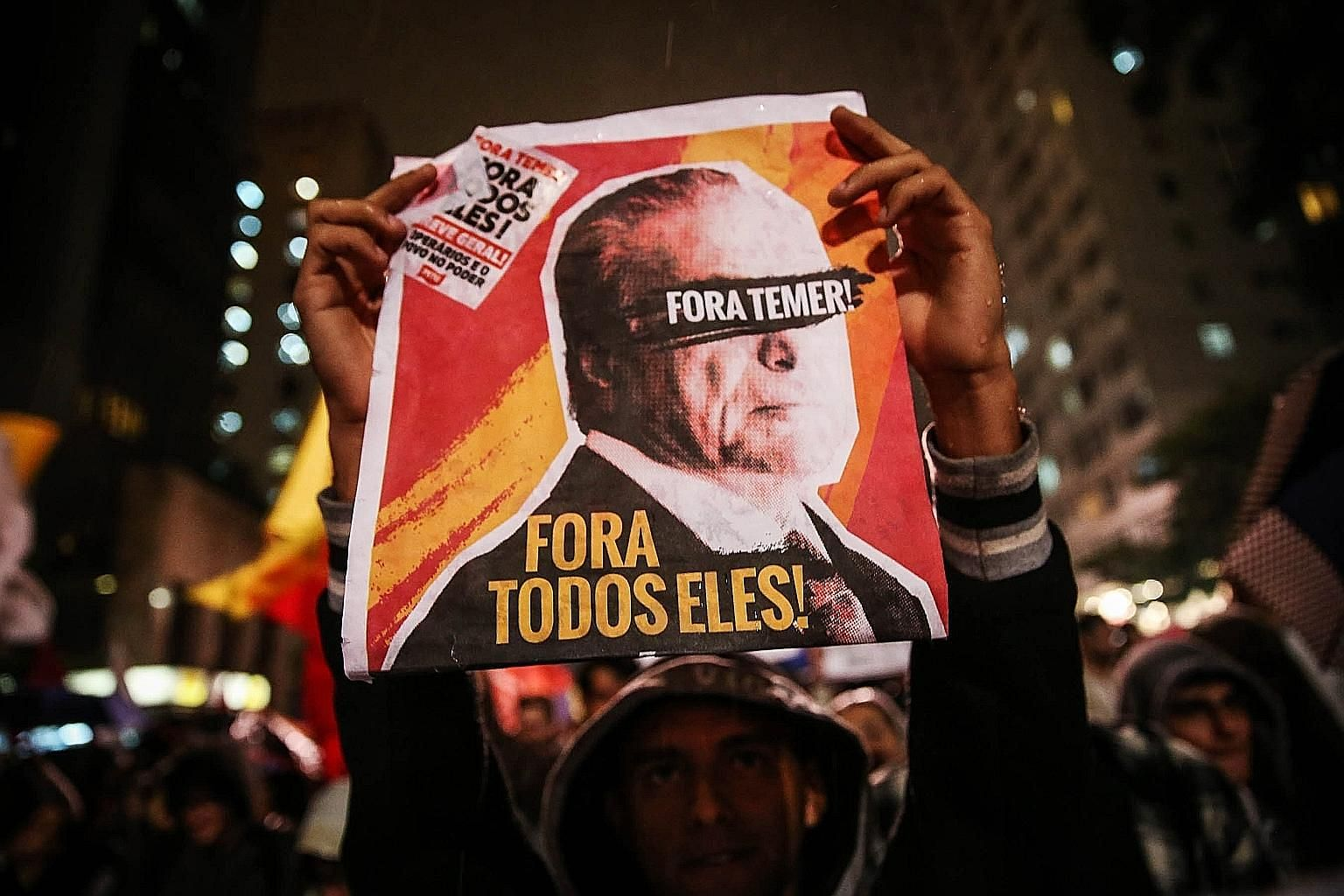 """A protester holding up a sign reading """"Out Temer! Out with them all!"""" in Sao Paulo, Brazil, yesterday. Thousands took to the streets in several cities to protest against the government of President Michel Temer, over allegations he is involved in a c"""