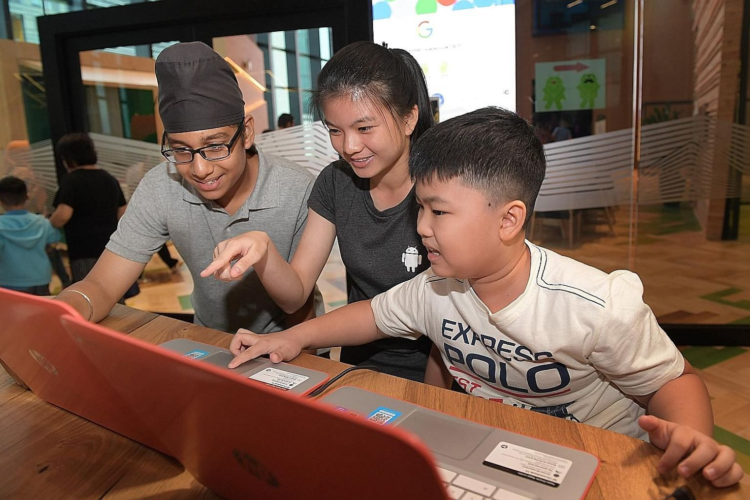 Keeret Singh Sandhu, 13, Celeste Low, 15, and Matthew Chua, 10, demonstrating their coding ability at the Google office in Pasir Panjang yesterday after completing a 10-week module.