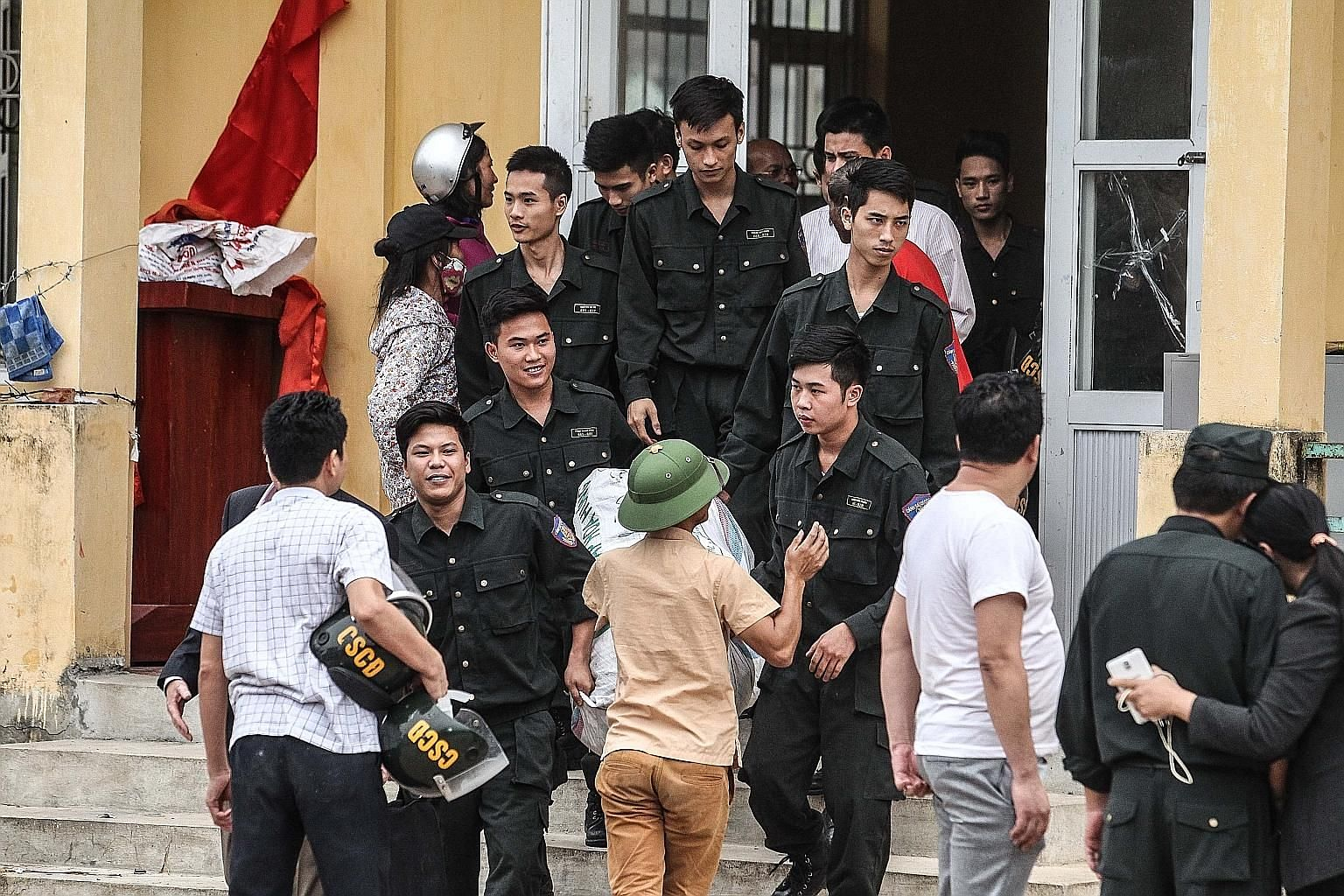 """Policemen who were held hostage by Vietnamese villagers over a land dispute being released from the Dong Tam communal house, on the outskirts of Hanoi, last month. A land-dispute protest in Dong Tam on April 20. The banner reads: """"The people of Dong"""
