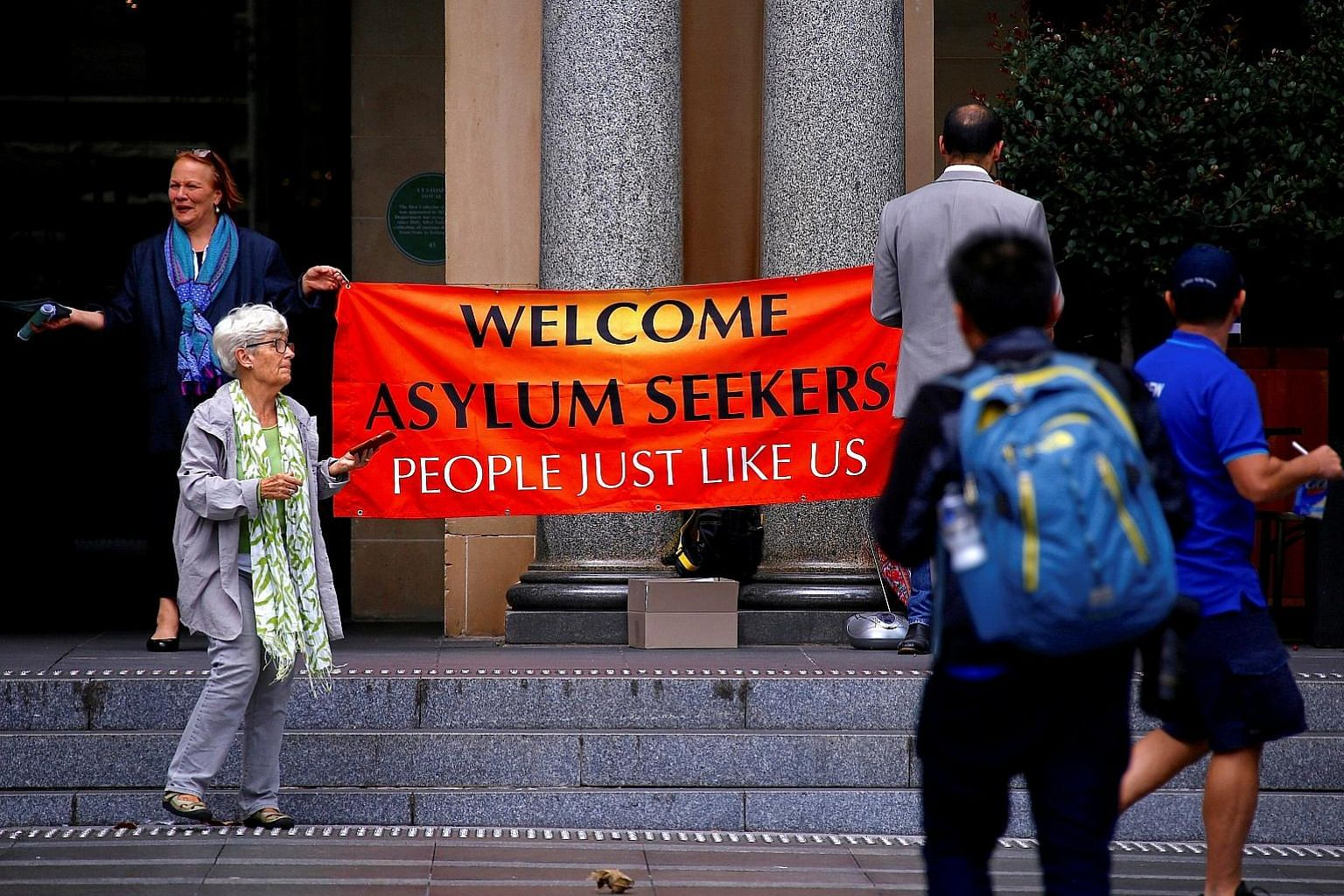 Refugee advocates displaying a banner on the steps of the Customs House building in Sydney on March 8. Some 50,000 people on 800 boats flooded into Australia seeking asylum before a clampdown in 2013. Of those, 7,500 have yet to present their cases f