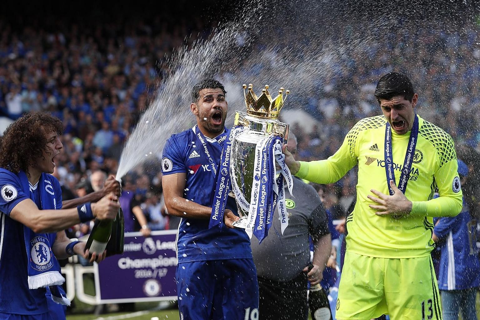 Above: Chelsea's Diego Costa and Thibaut Courtois (right) are sprayed with champagne by team-mate David Luiz during the festivities after their 5-1 win over Sunderland. Left: John Terry gets a guard of honour after his premeditated substitution in th