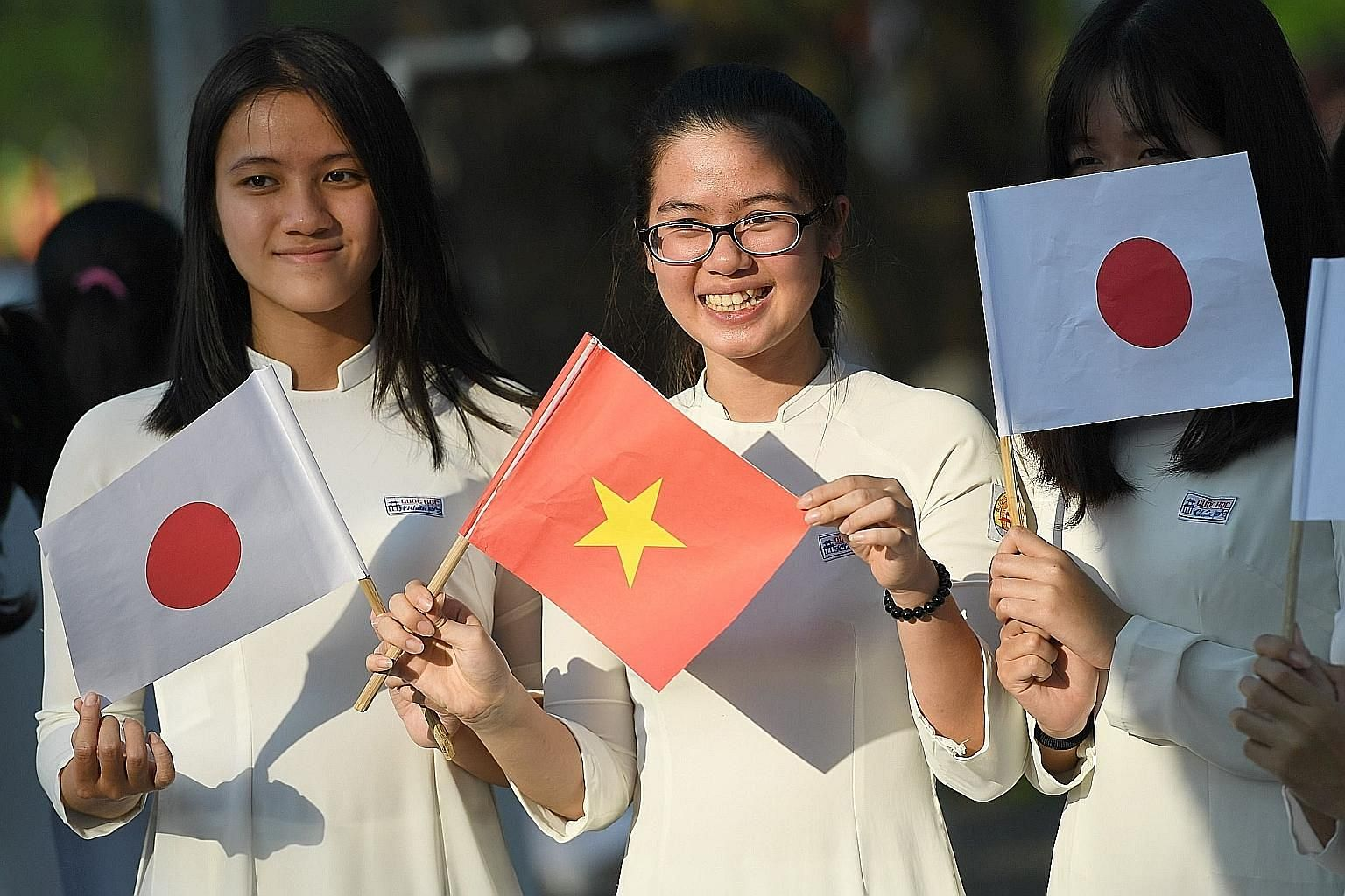 Students waiting on a street in Hue, Vietnam, to welcome Japan's Emperor Akihito and Empress Michiko during their March visit.