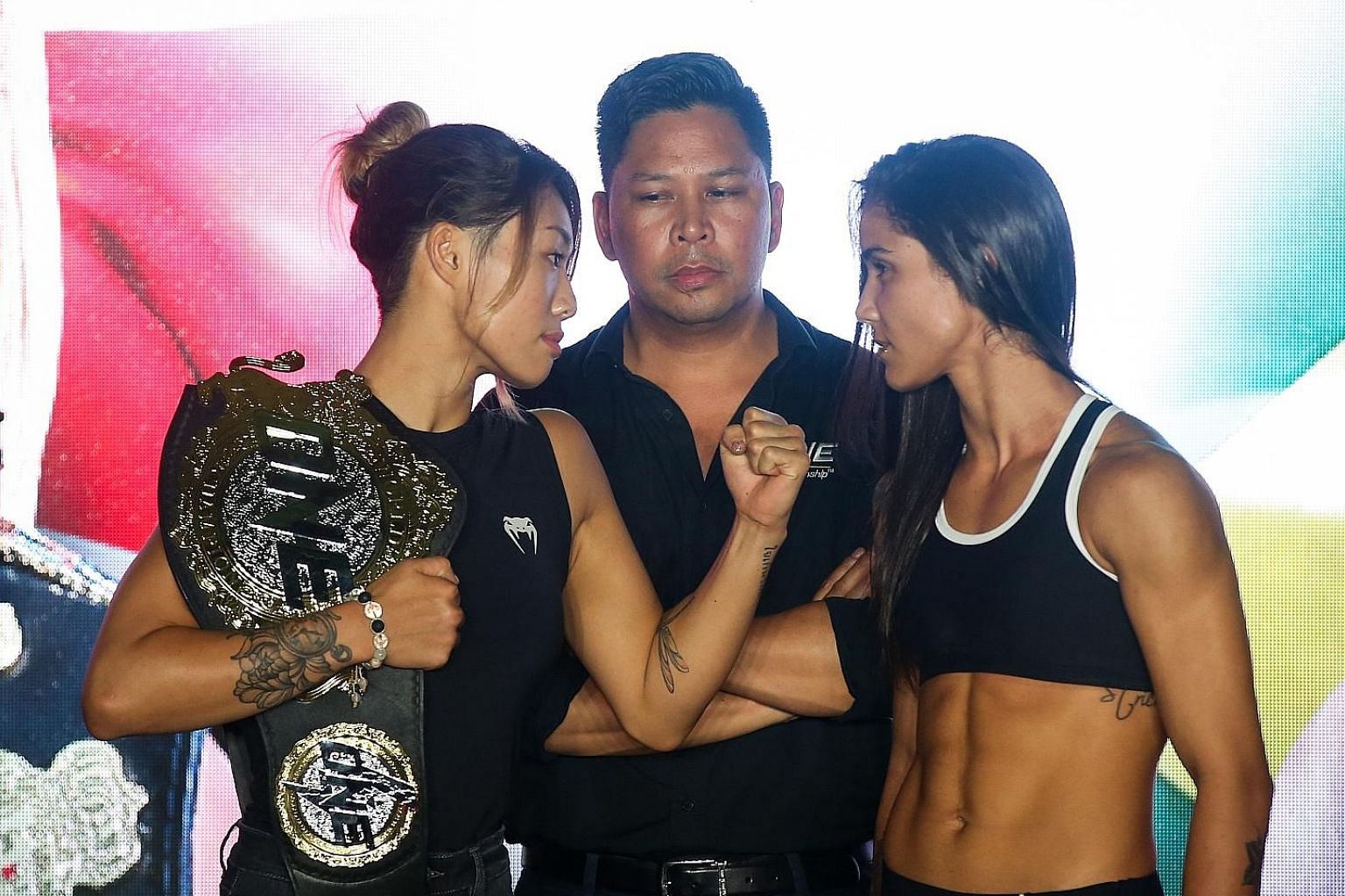With her championship belt slung over her shoulder, Angela Lee (left) faces off against Istela Nunes (right). Lee said her talent as a fast starter will be crucial in winning today.