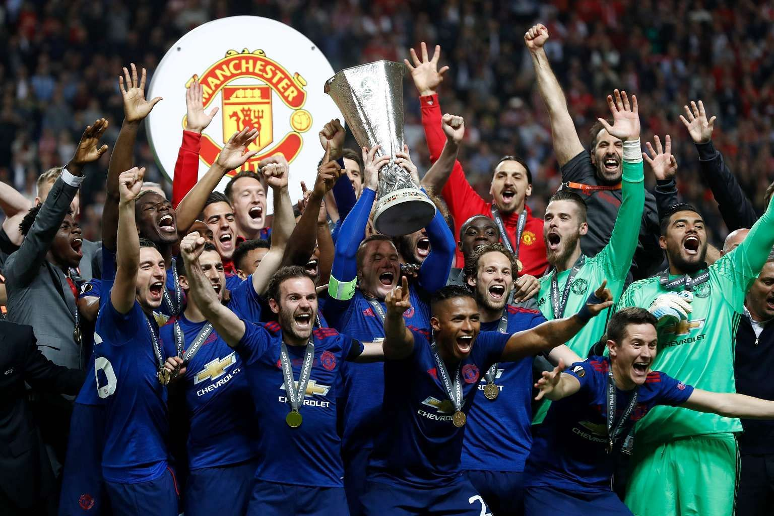 Above: Manchester United players with the Europa League trophy after beating Ajax Amsterdam 2-0 in Stockholm on Wednesday. Left: Jose Mourinho celebrates with members of his coaching staff.