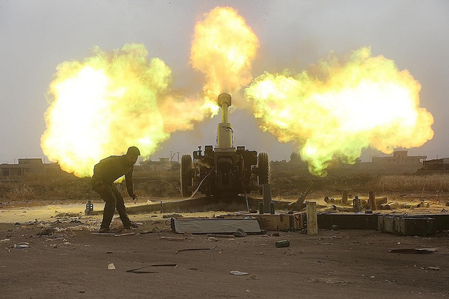 Popular Mobilisation Forces personnel firing at ISIS militants during a battle on the outskirts of Al-Ba'aj, west of Mosul, on Friday. The United States-backed offensive on Mosul, now in its eighth month, has taken longer than planned as the militant