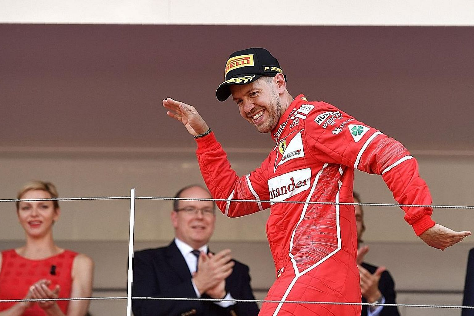 Ferrari's Sebastian Vettel celebrating on the podium after winning in Monaco, watched by Prince Albert II, Princess Charlene and other dignitaries.