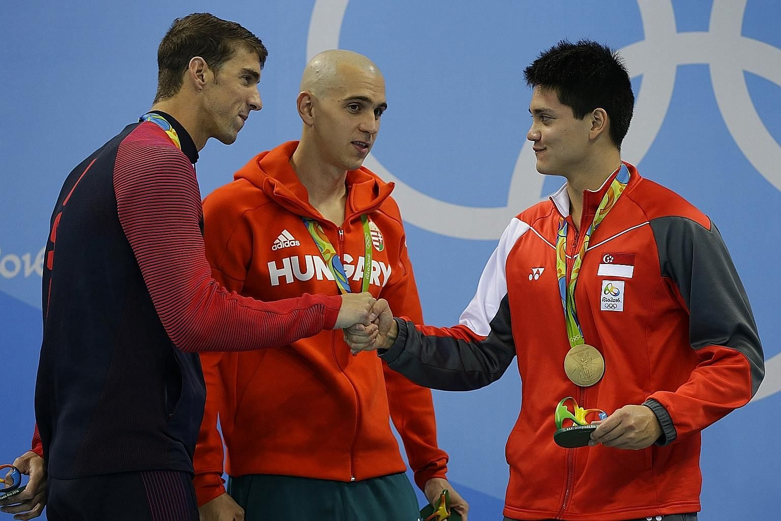 American Michael Phelps, the greatest swimmer in history, congratulating Olympic champion Joseph Schooling, as Hungary's Laszlo Cseh looks on after the men's 100m butterfly final. Chad le Clos also shared the silver.