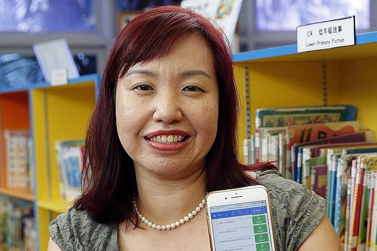 Edgefield Primary School teacher Tan Pin Pin uses a mobile app on her phone to take down her pupils' attendance.