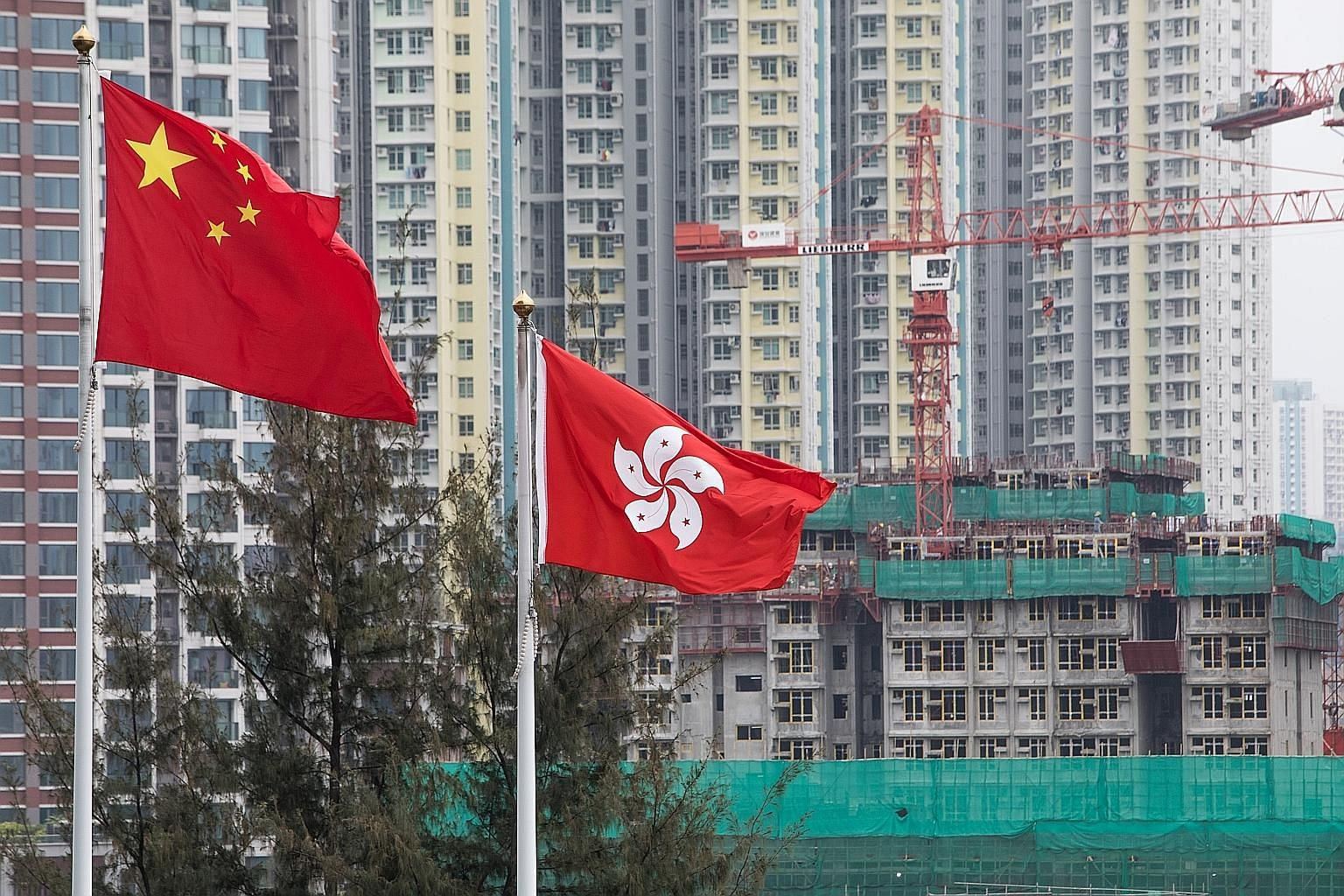 The flags of China (left) and Hong Kong fluttering in front a construction site in Hong Kong. Chinese developers, including HNA and Logan Property, have outbid local contenders for expensive land, snapping up all HK$37 billion (S$6.6 billion) worth